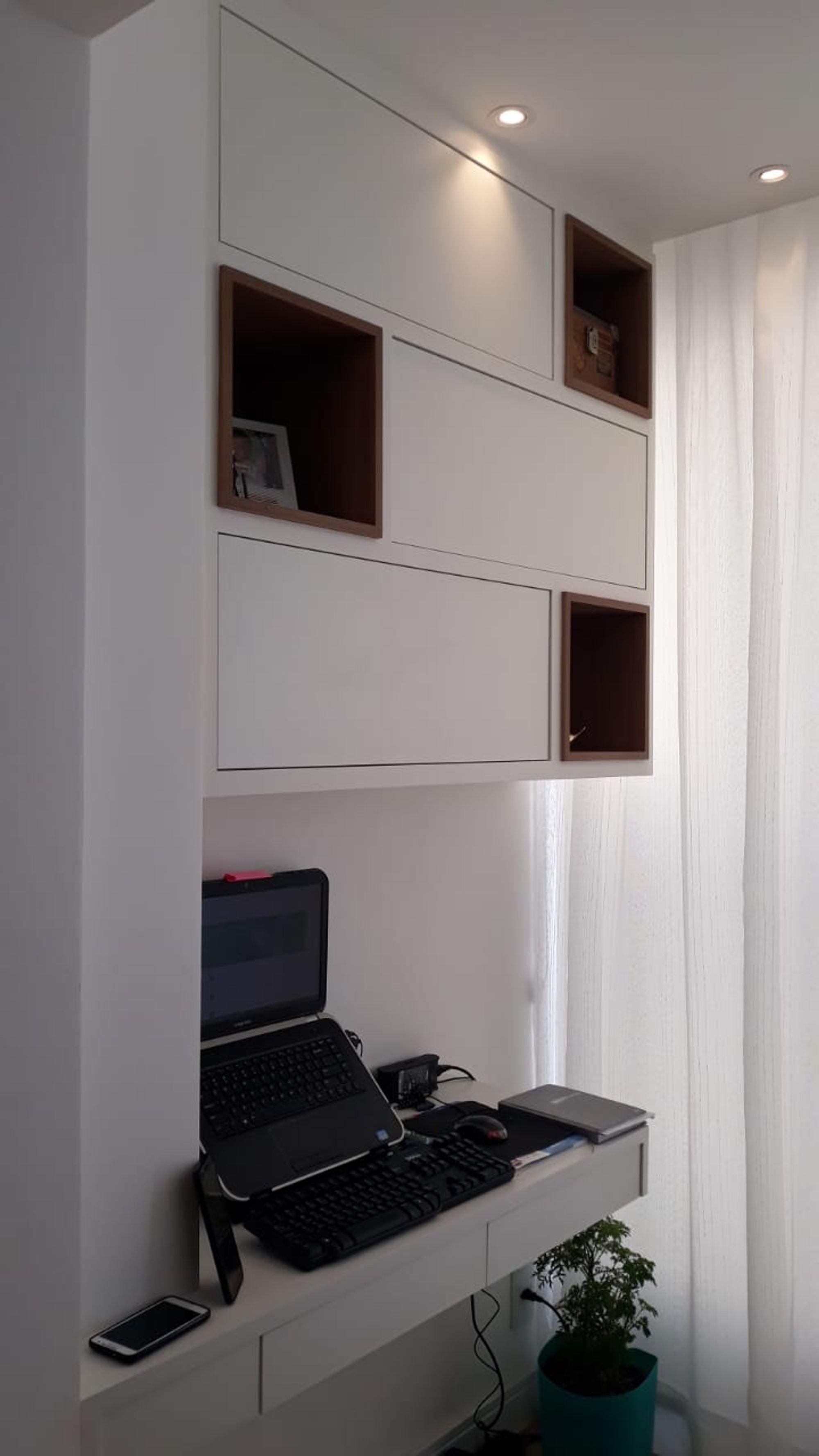 Foto de Sala com vaso de planta, mouse, teclado, televisão, celular, computador portátil