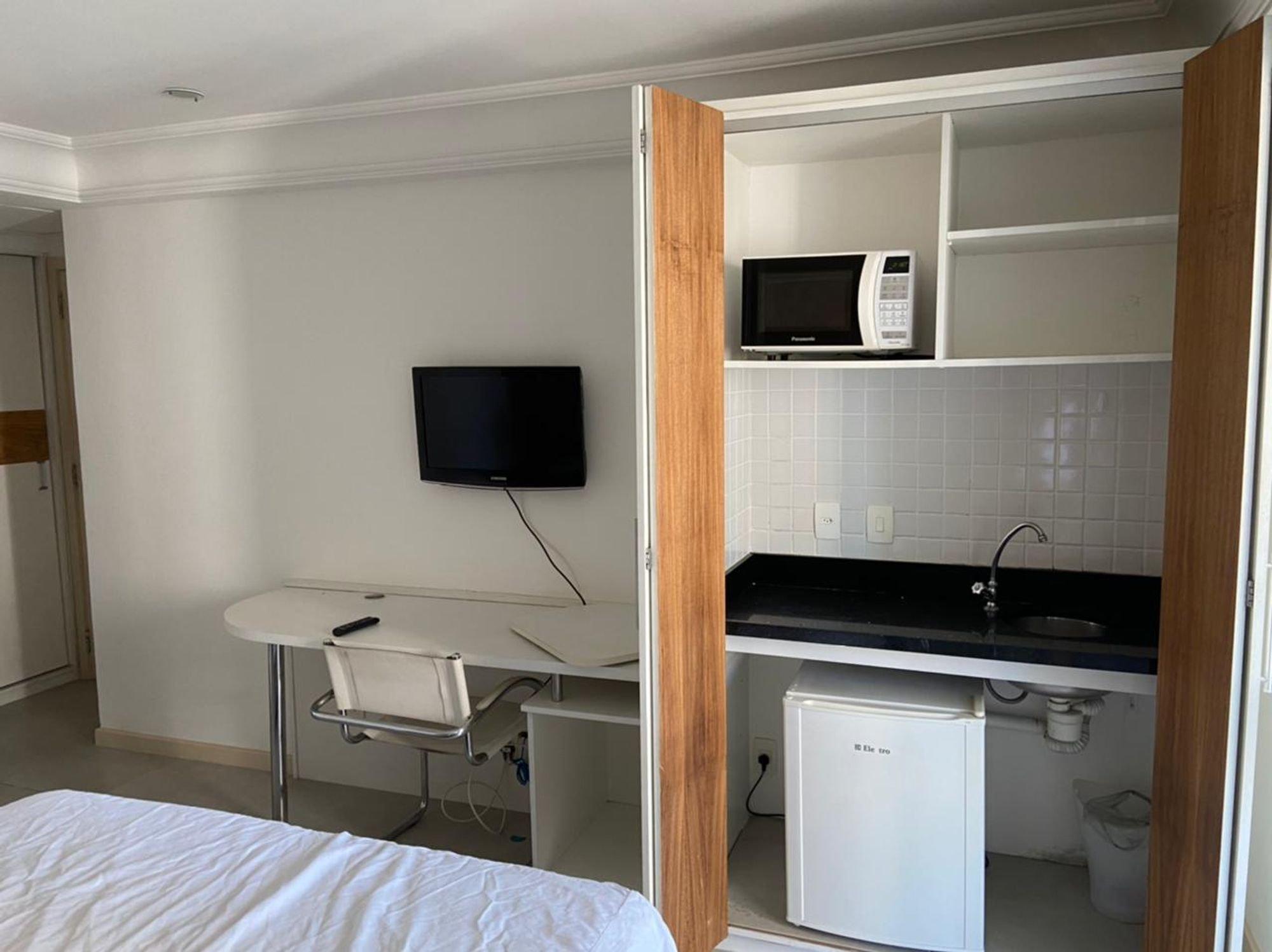 Foto de Cozinha com cama, televisão, computador portátil, microondas