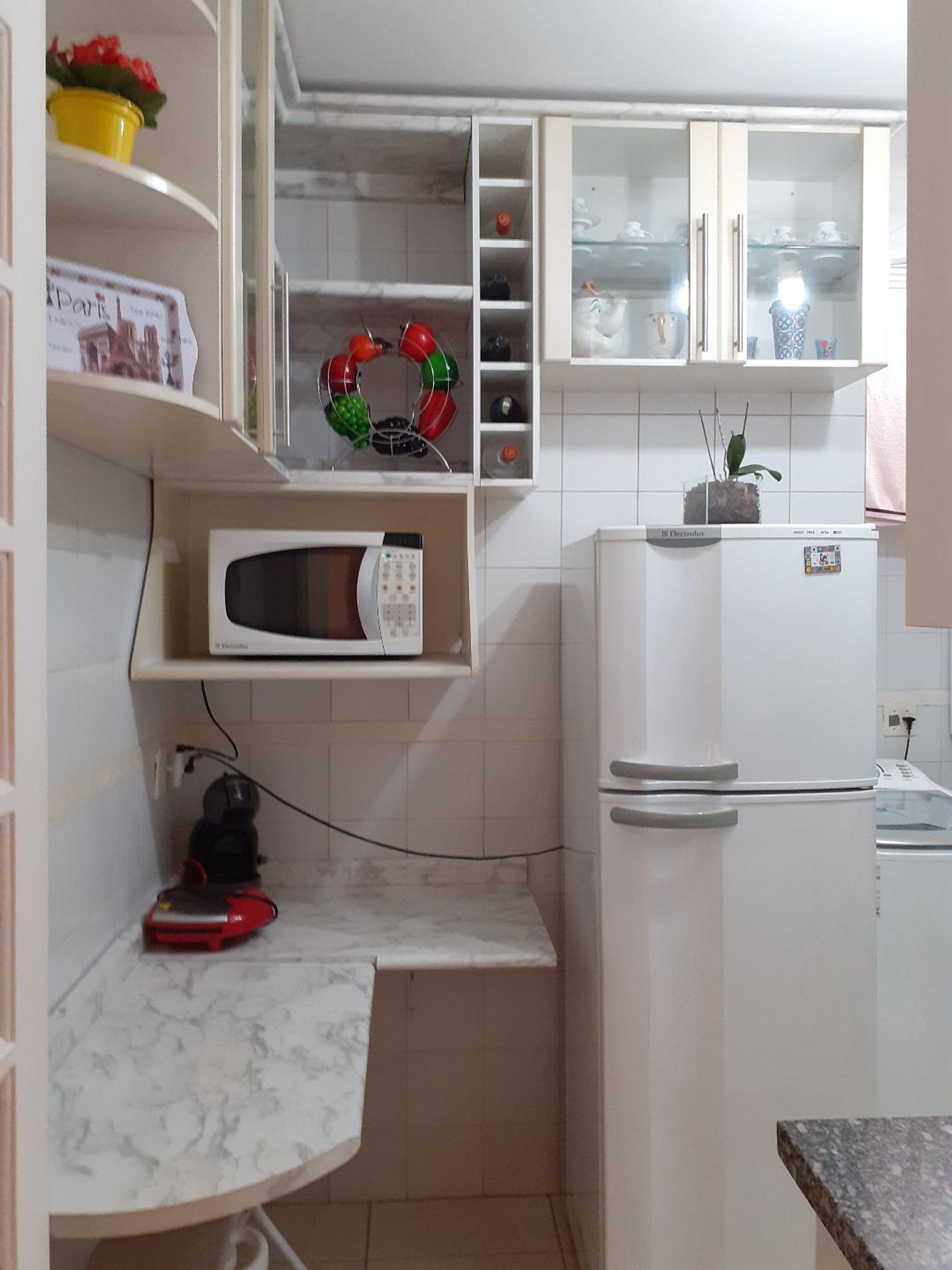 Foto de Cozinha com garrafa, tigela, geladeira, microondas