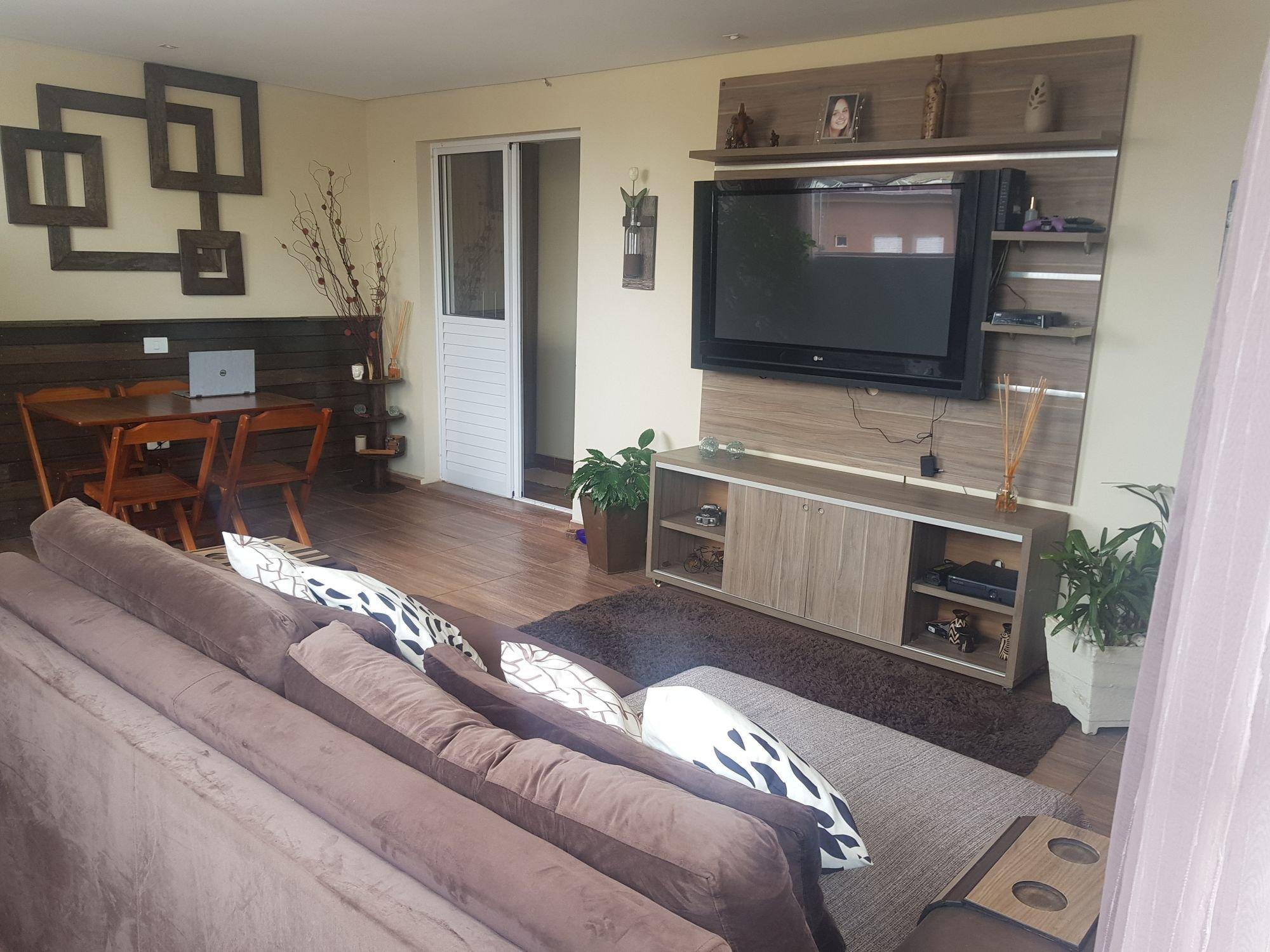 Foto de Sala com vaso de planta, sofá, televisão, cadeira, mesa de jantar