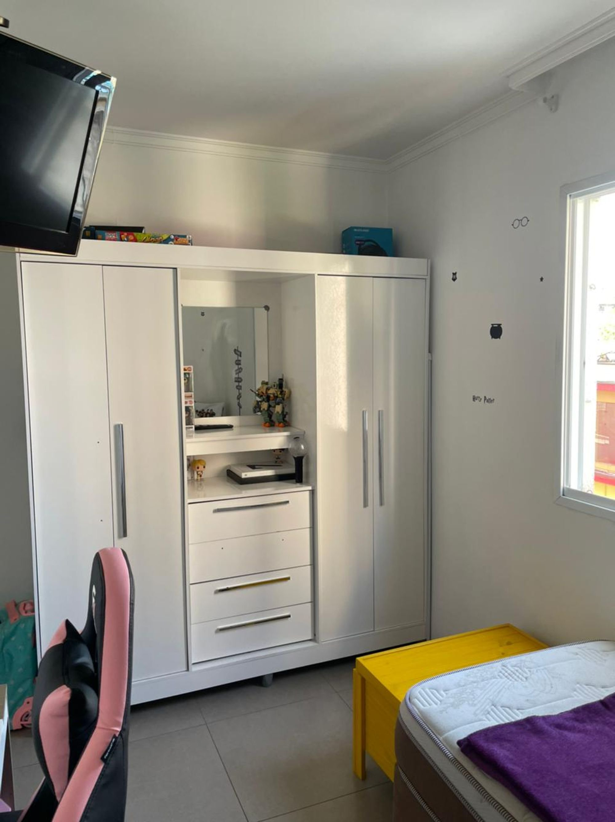 Foto de Quarto com cama, televisão, geladeira, cadeira