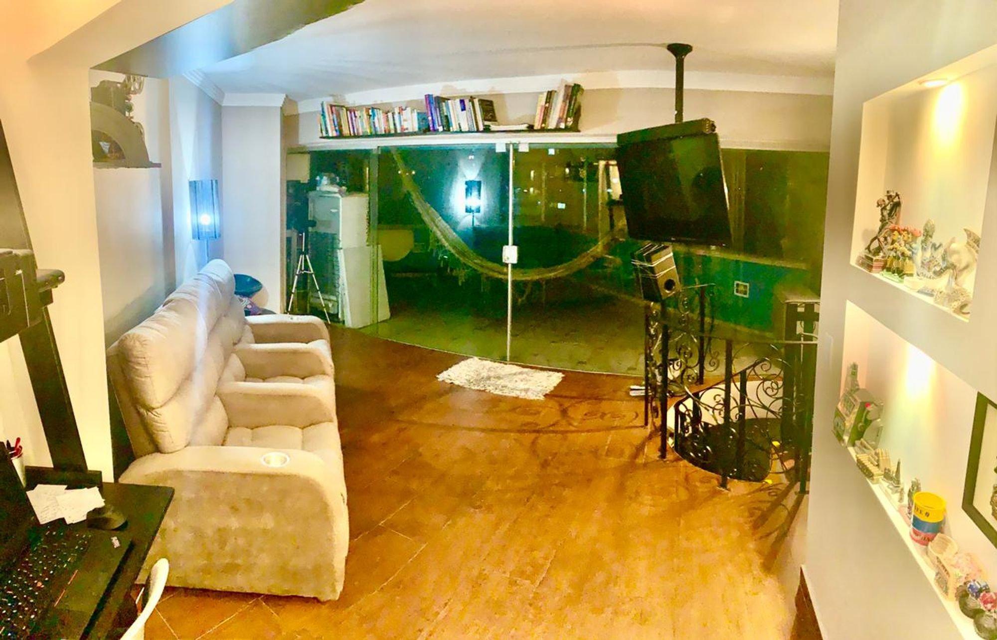 Foto de Sala com sofá, televisão, garrafa, computador portátil, livro