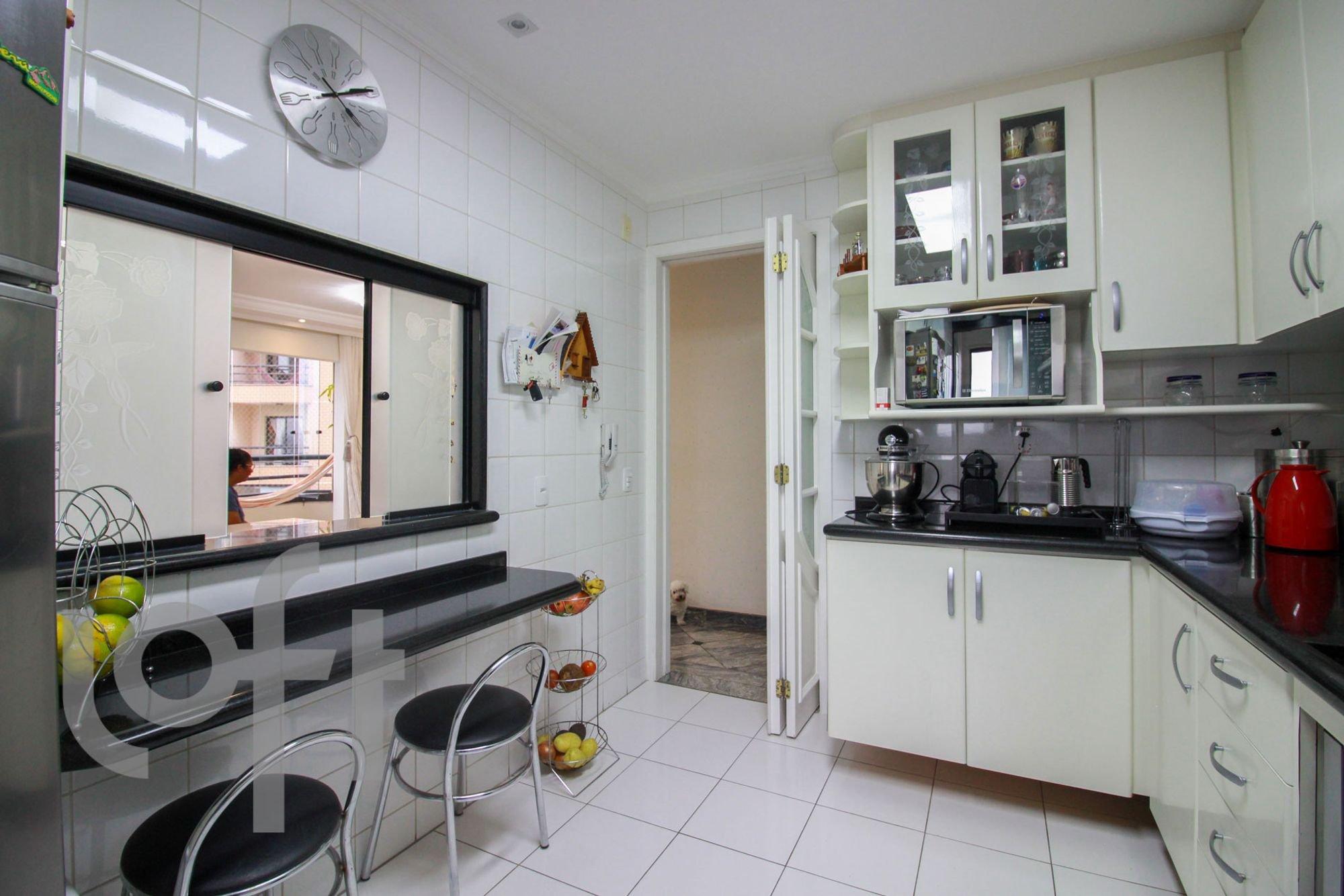 Foto de Cozinha com garrafa, relógio, pia, cadeira, livro