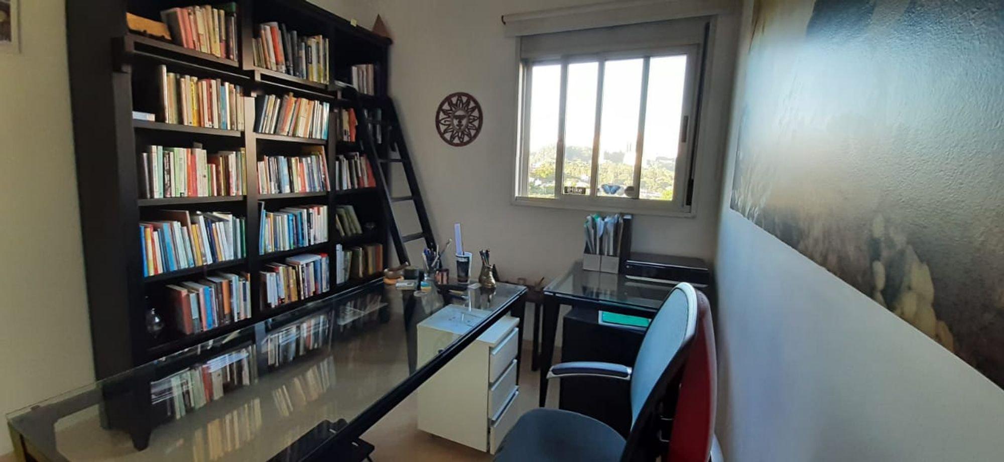 Foto de Sala com relógio, garrafa, cadeira, livro