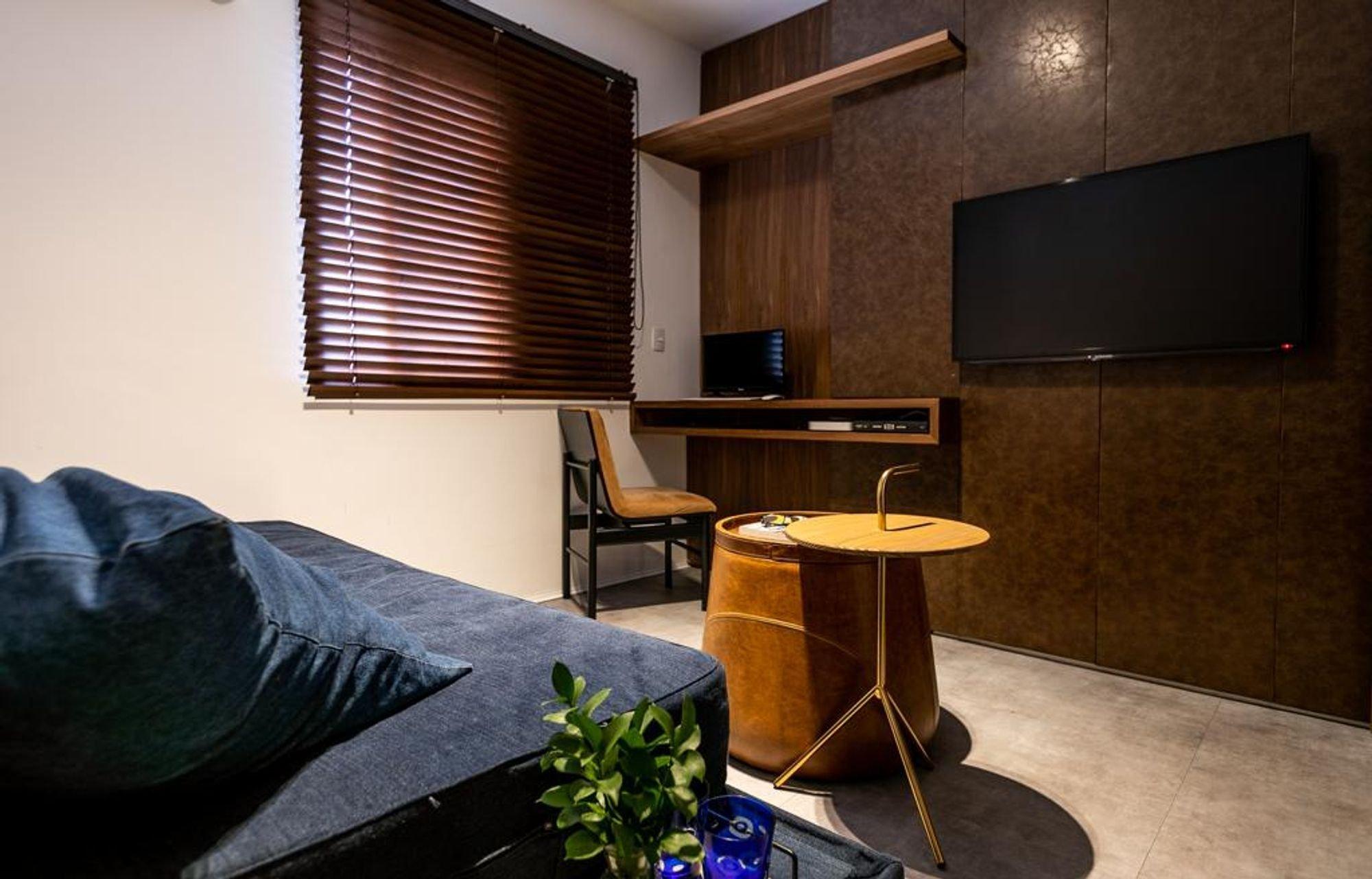 Foto de Sala com vaso de planta, cama, televisão, cadeira