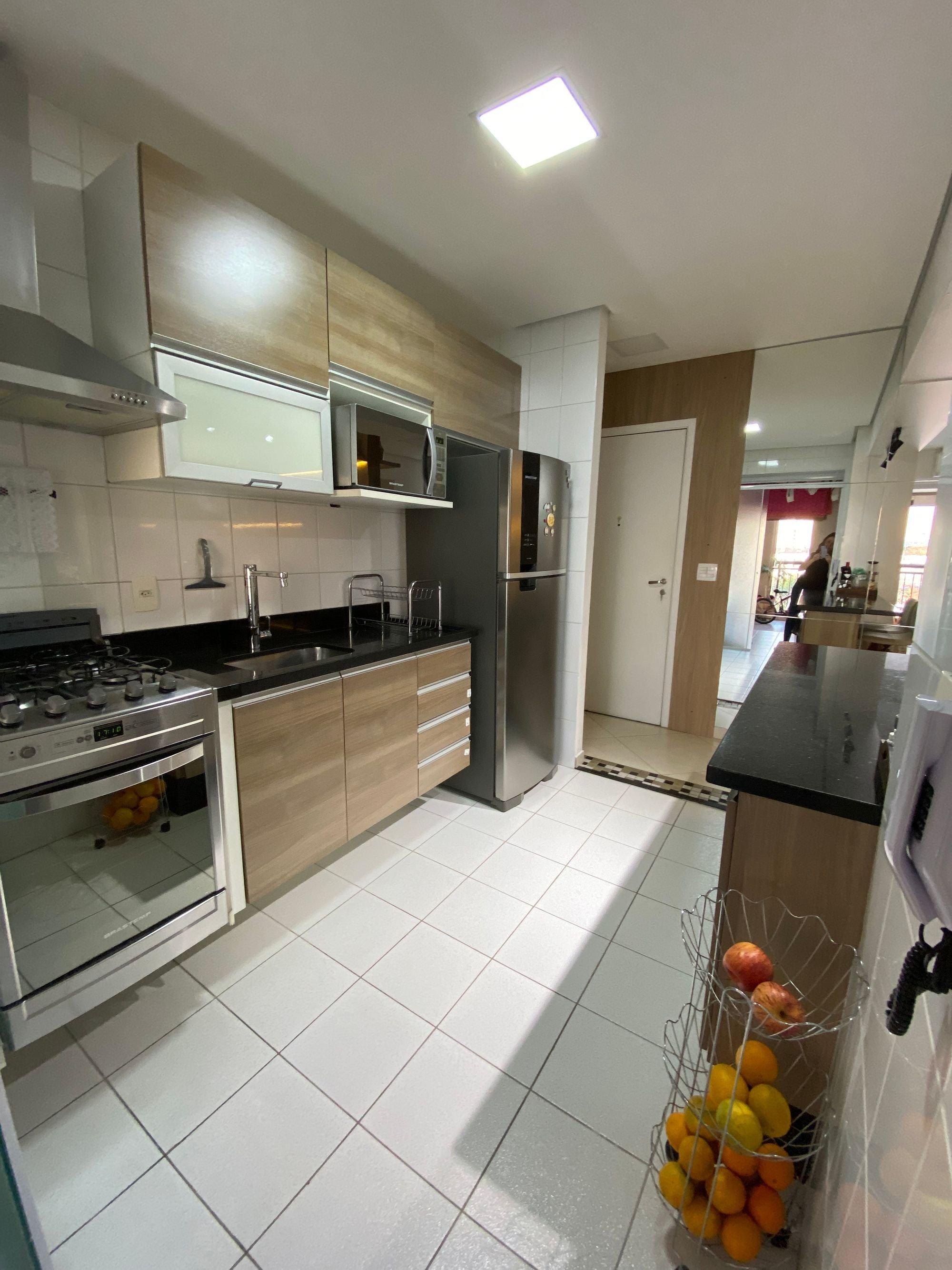 Foto de Cozinha com forno, geladeira, pessoa, microondas