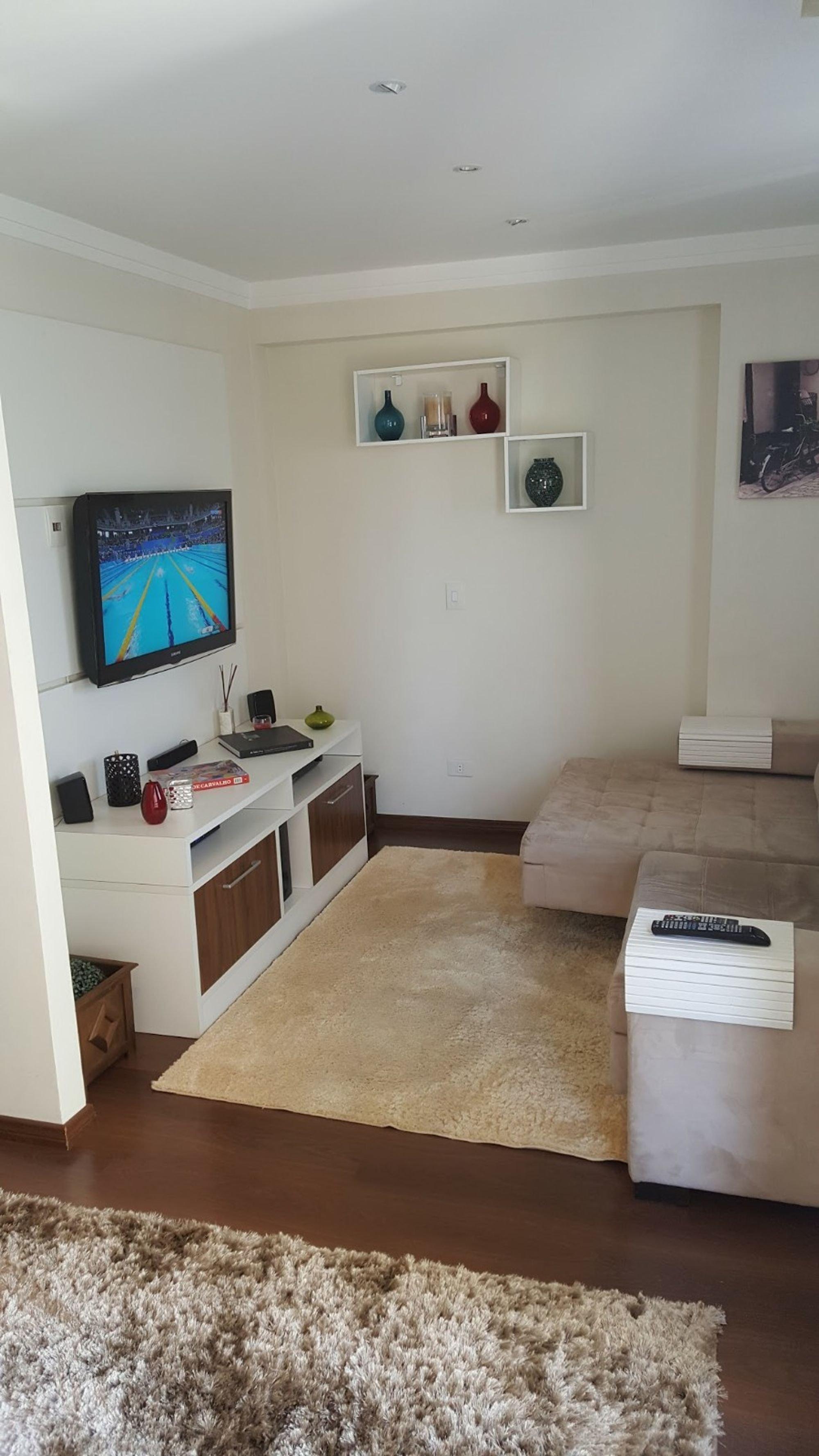Foto de Sala com sofá, televisão, vaso, banco
