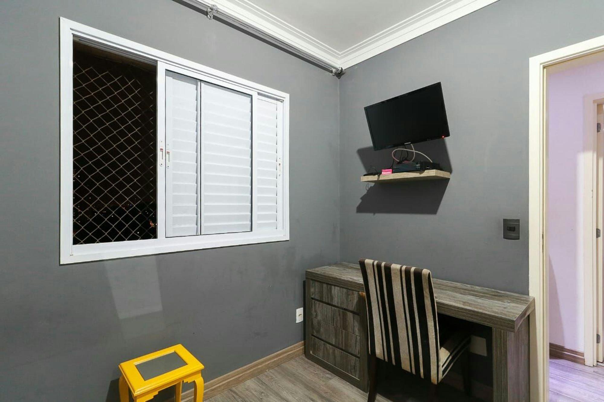 Foto de Quarto com televisão, cadeira