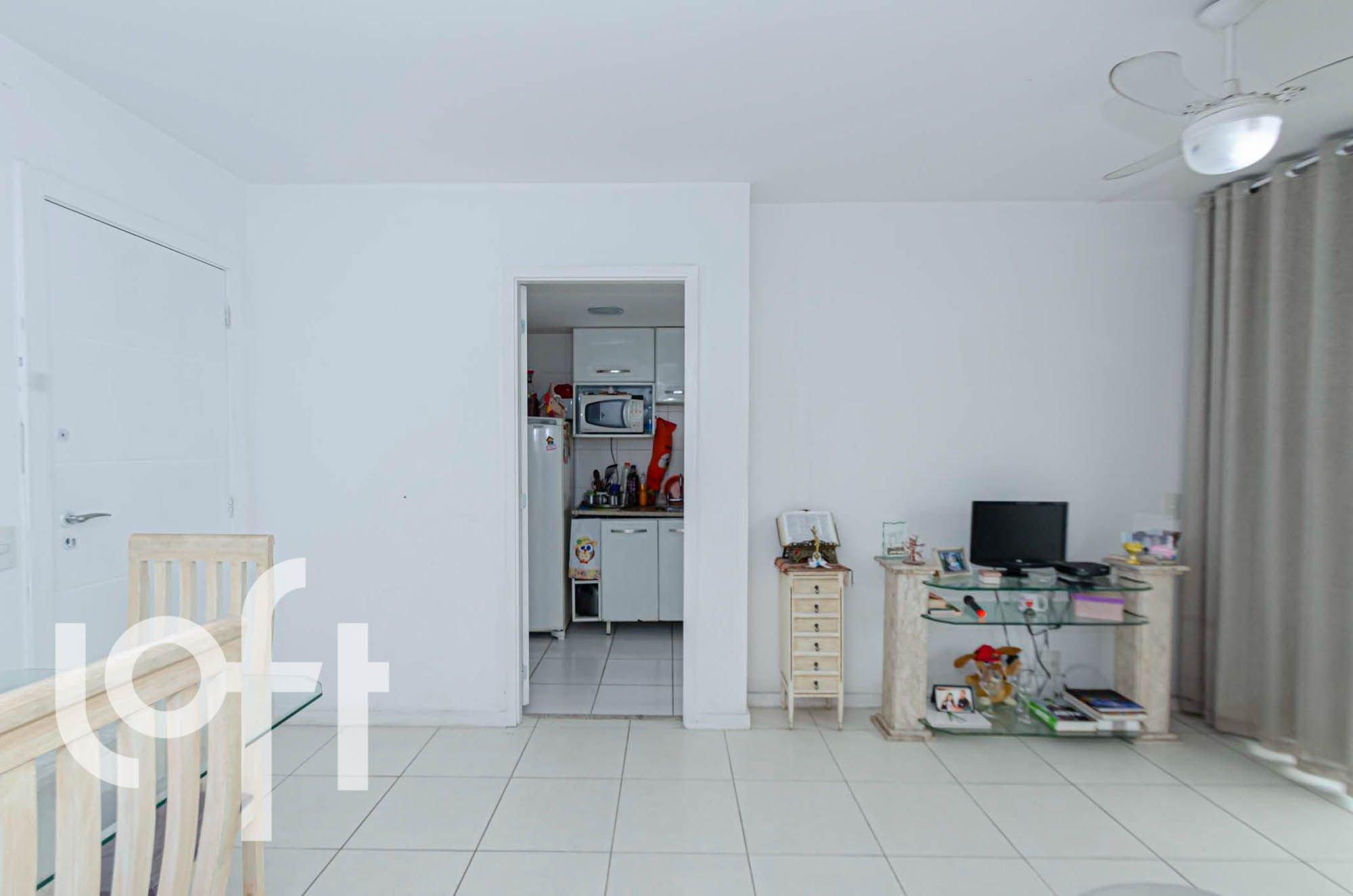 Foto de Sala com televisão, garrafa, geladeira, livro