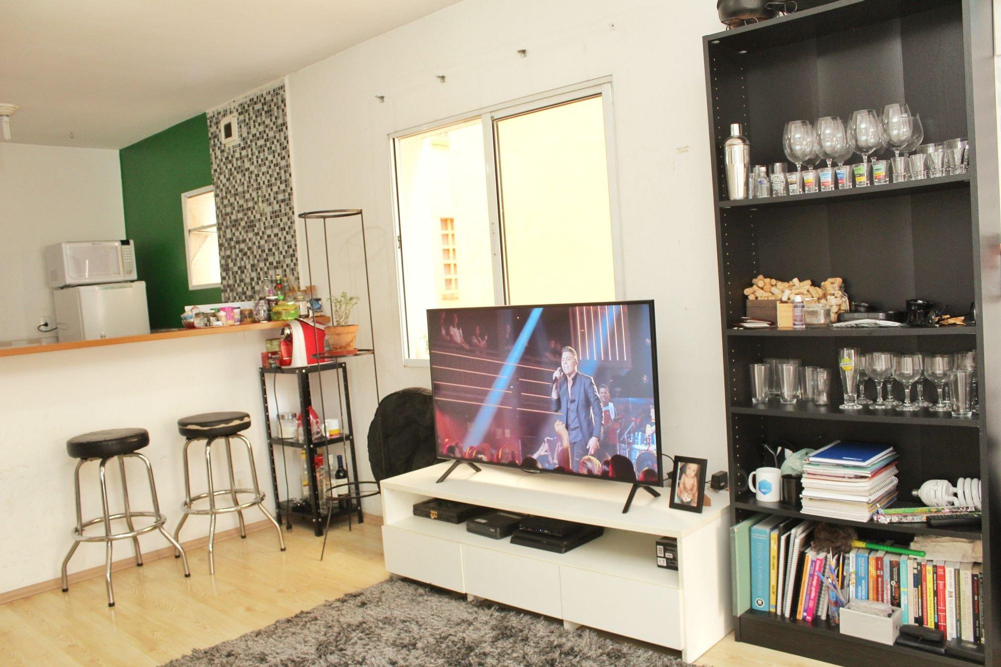 Foto de Sala com copo de vinho, televisão, cadeira, livro, garrafa, microondas, xícara