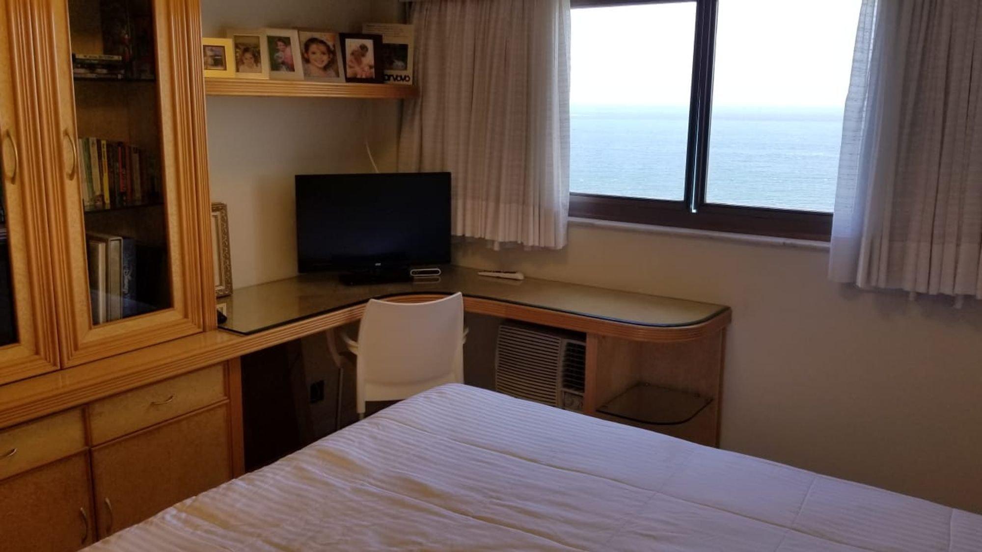 Foto de Quarto com cama, televisão, cadeira, livro