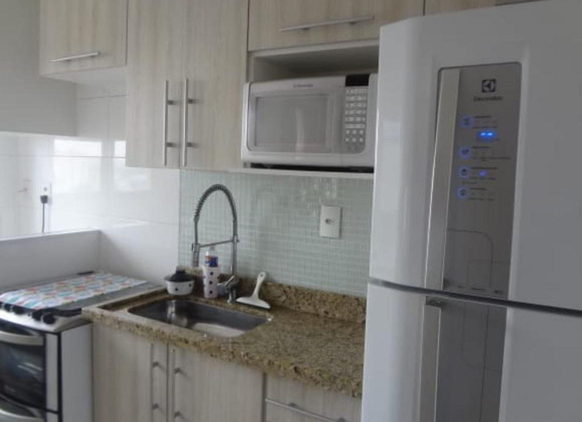 Foto de Cozinha com forno, geladeira, pia, microondas