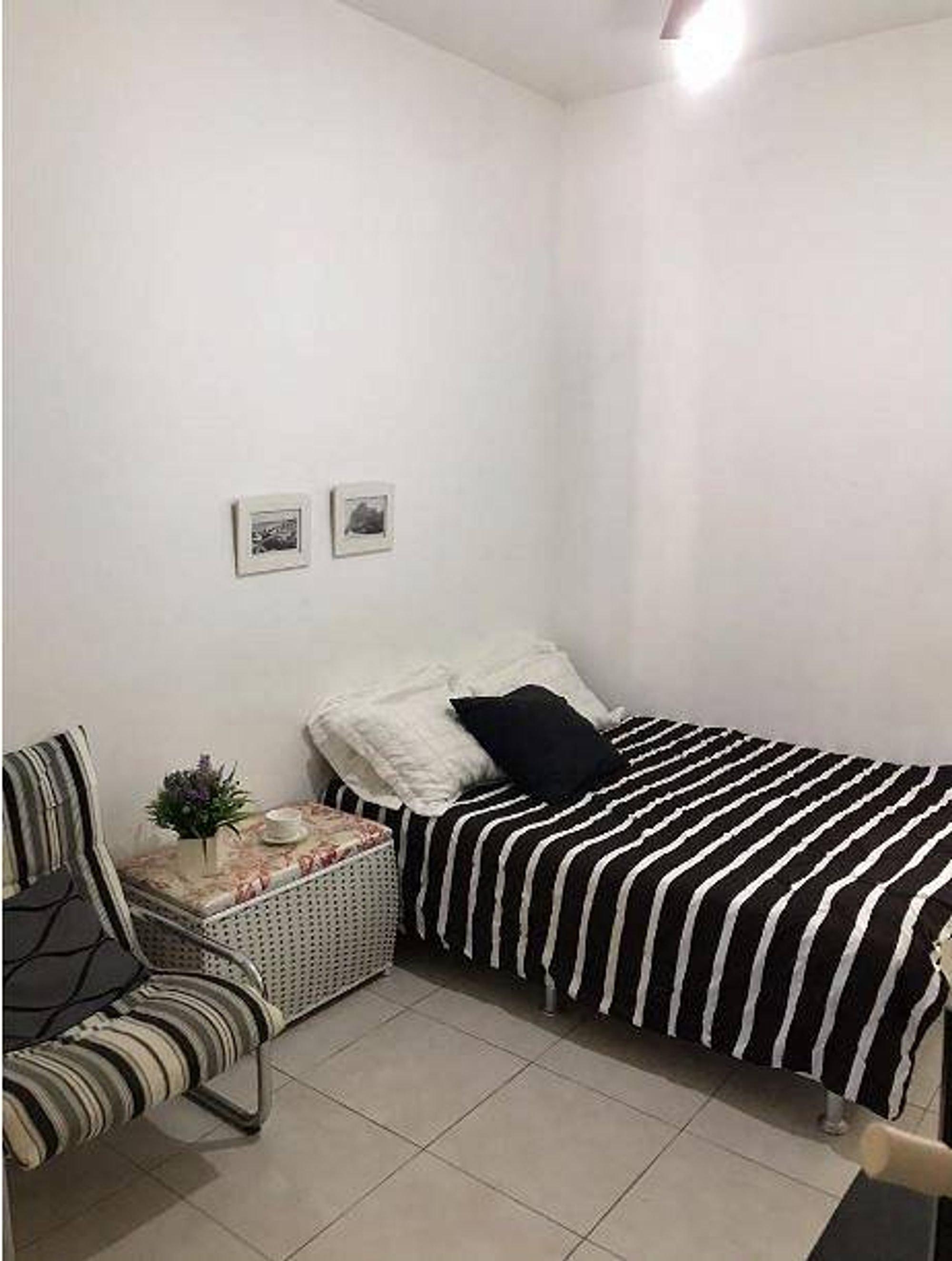 Foto de Quarto com cama, vaso de planta, sofá