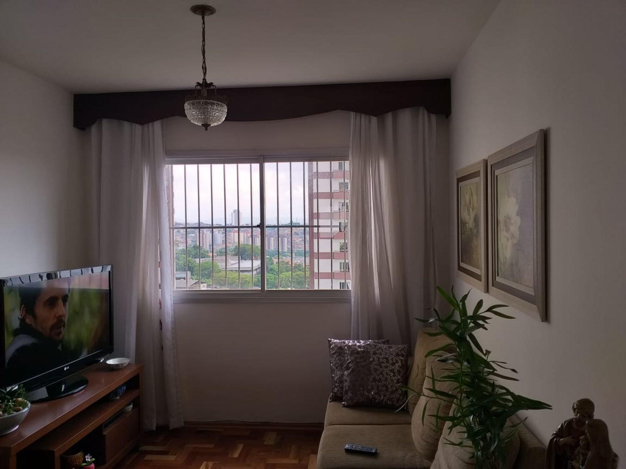 Foto de Sala com vaso de planta, sofá, televisão, controle remoto