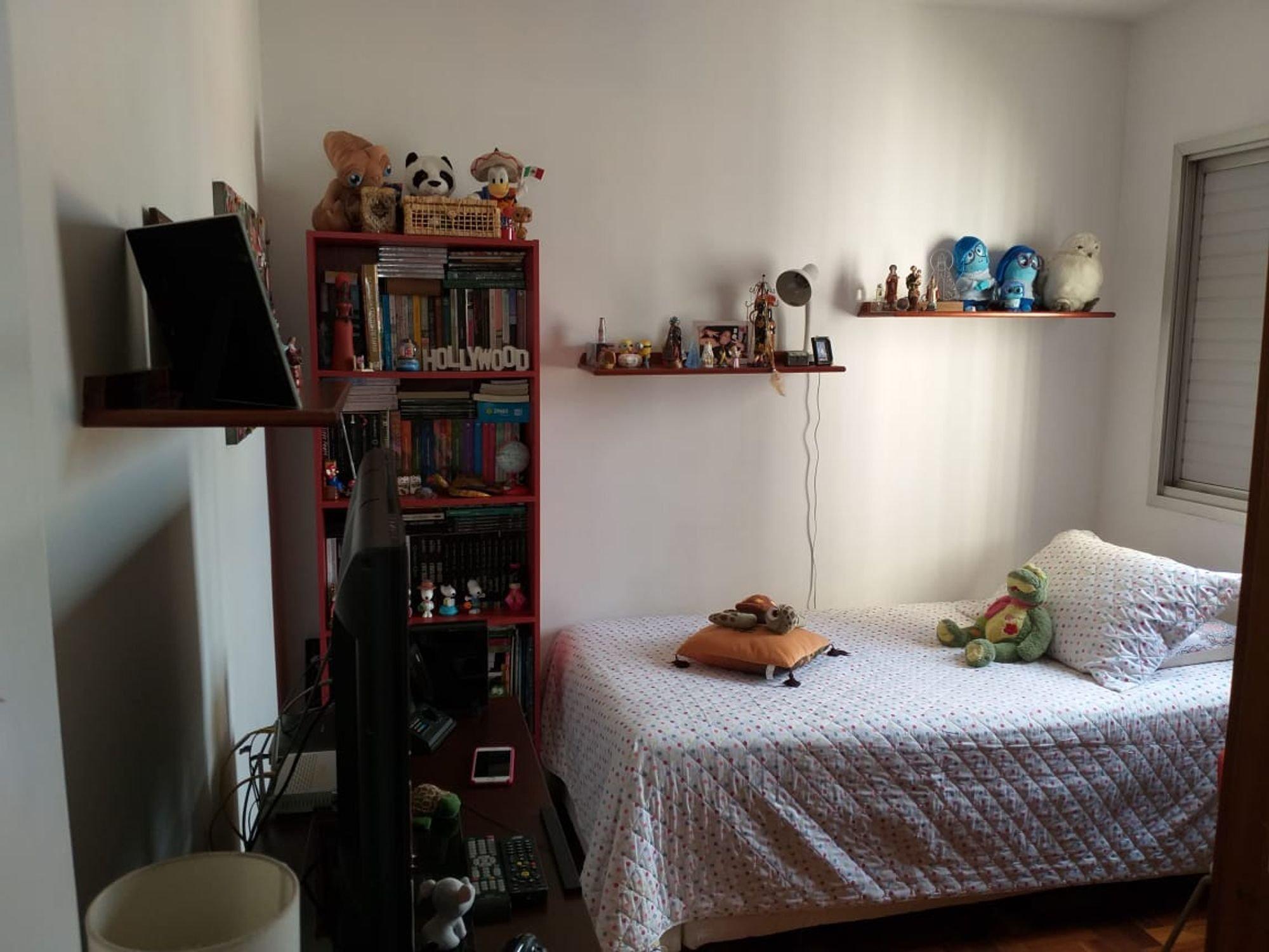 Foto de Quarto com cama, urso teddy, livro