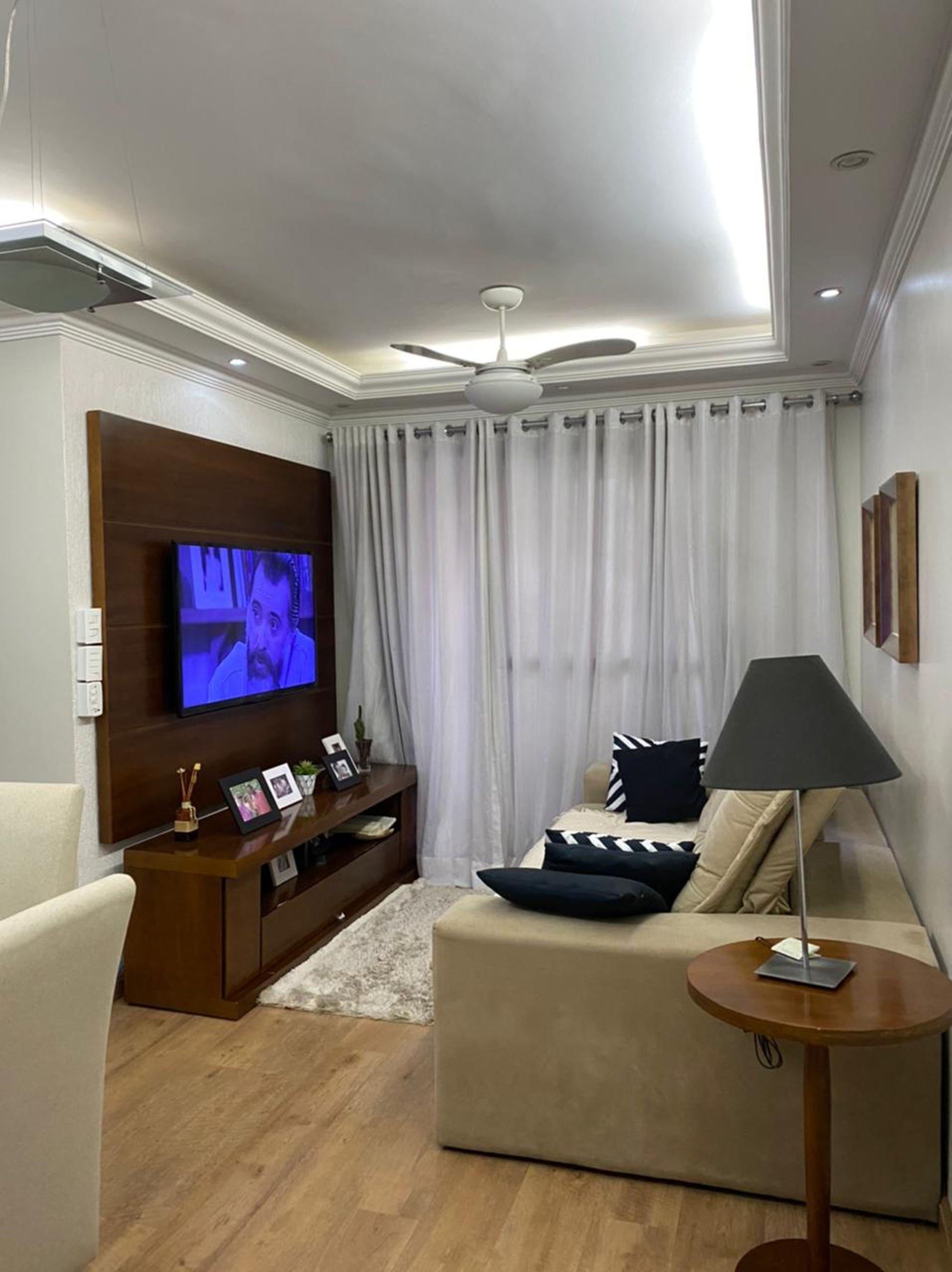 Foto de Sala com copo de vinho, sofá, bolsa, televisão, pessoa