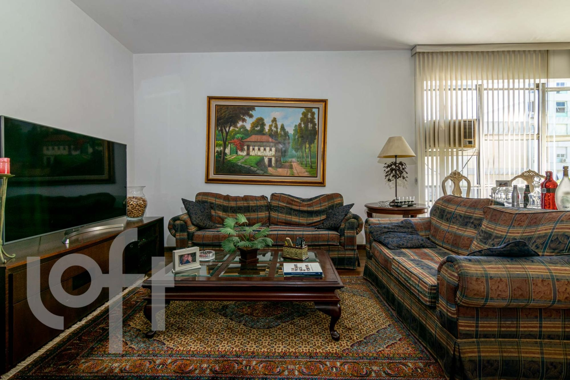 Foto de Sala com sofá, televisão, vaso, garrafa, livro