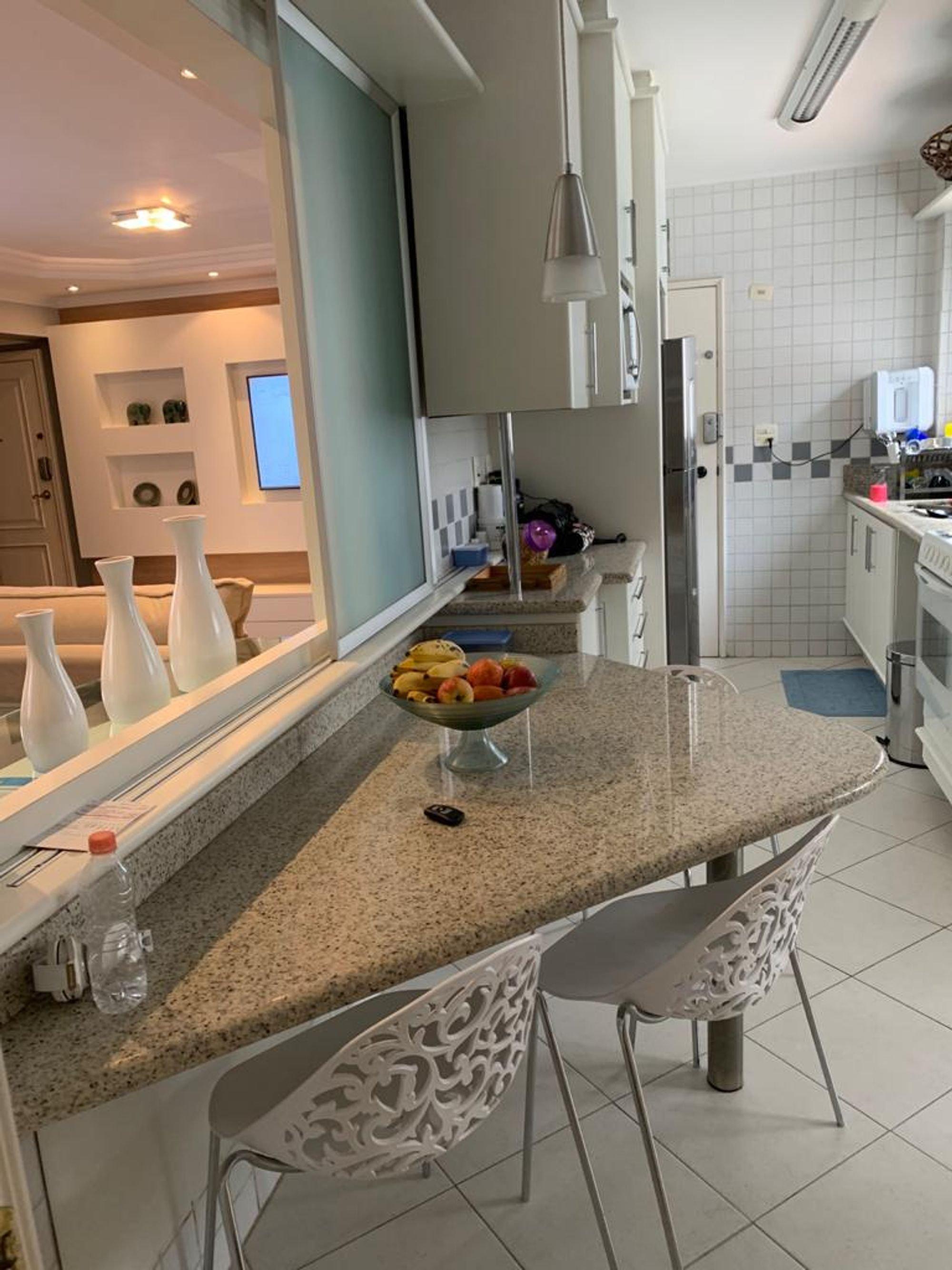 Foto de Cozinha com maçã, forno, cadeira, mesa de jantar, vaso, garrafa, tigela, geladeira