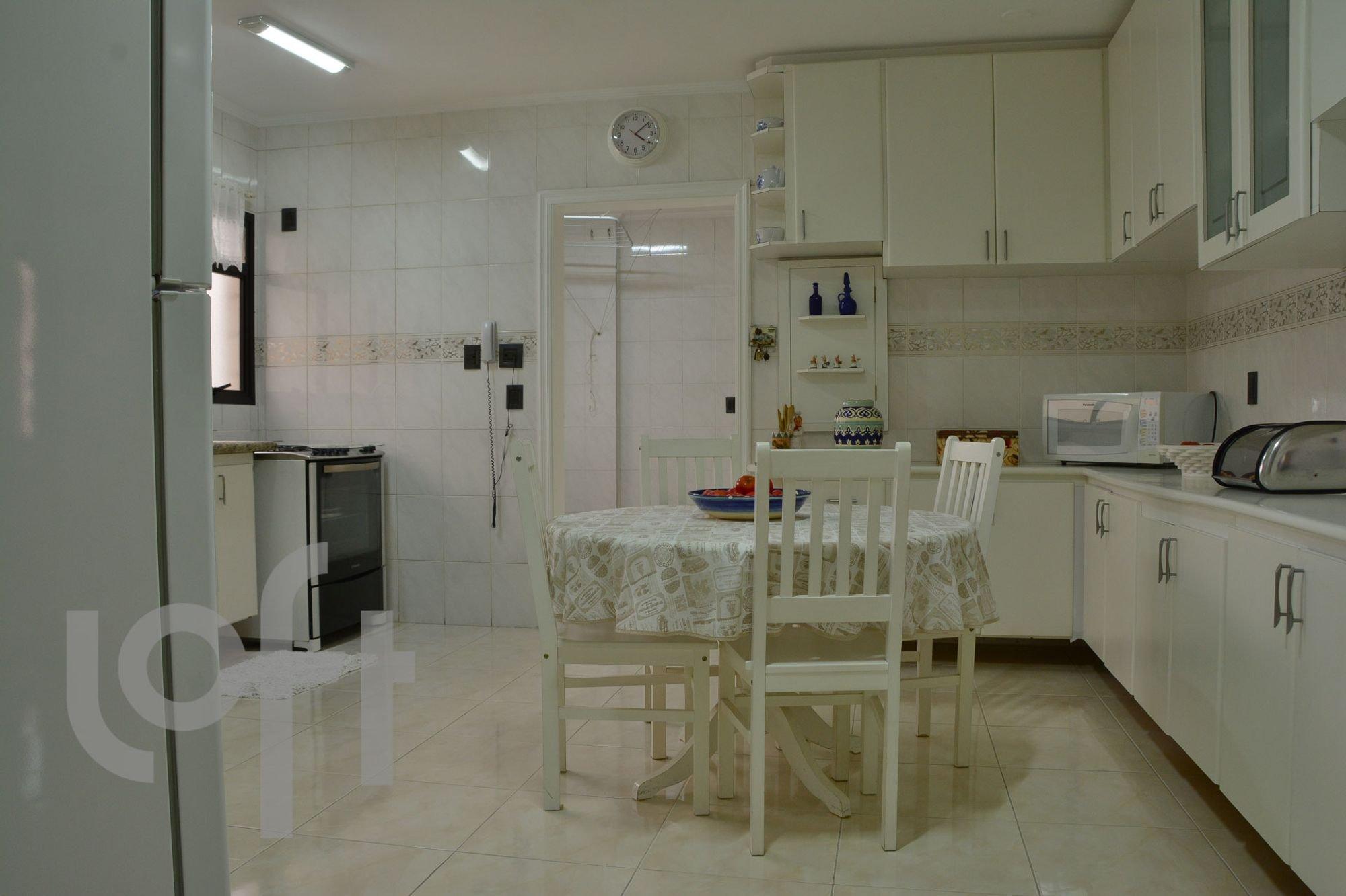 Foto de Cozinha com relógio, garrafa, tigela, cadeira, microondas, mesa de jantar