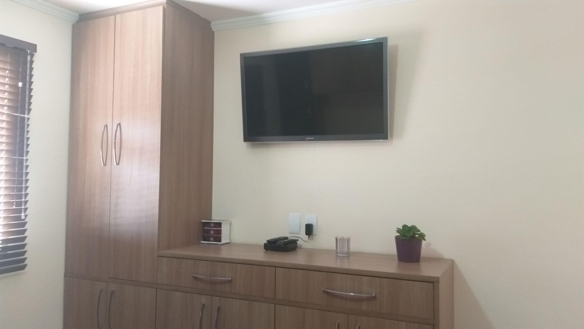 Foto de Quarto com vaso de planta, televisão