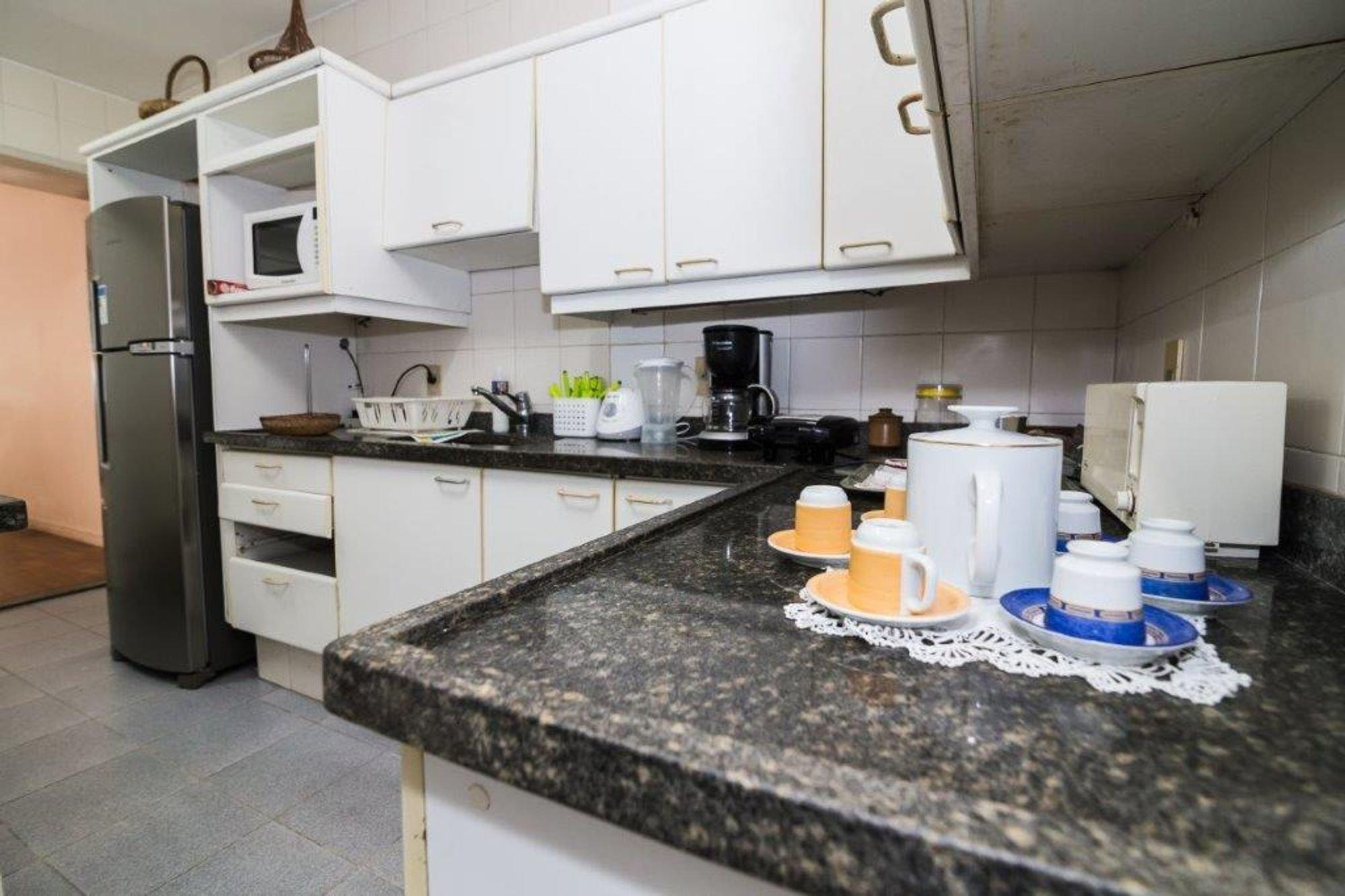 Foto de Cozinha com garrafa, tigela, geladeira, microondas, xícara