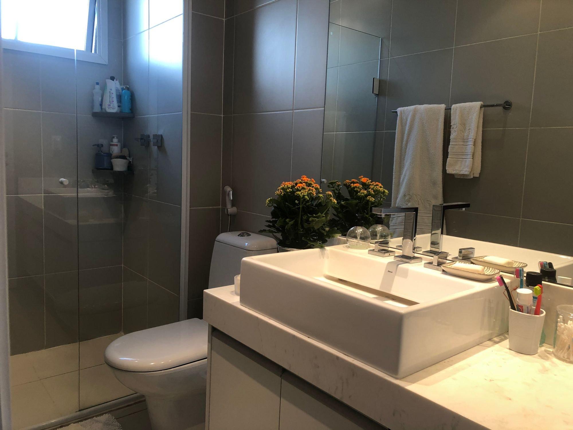 Foto de Banheiro com vaso de planta, escova de dente, vaso sanitário, garrafa, pia, xícara