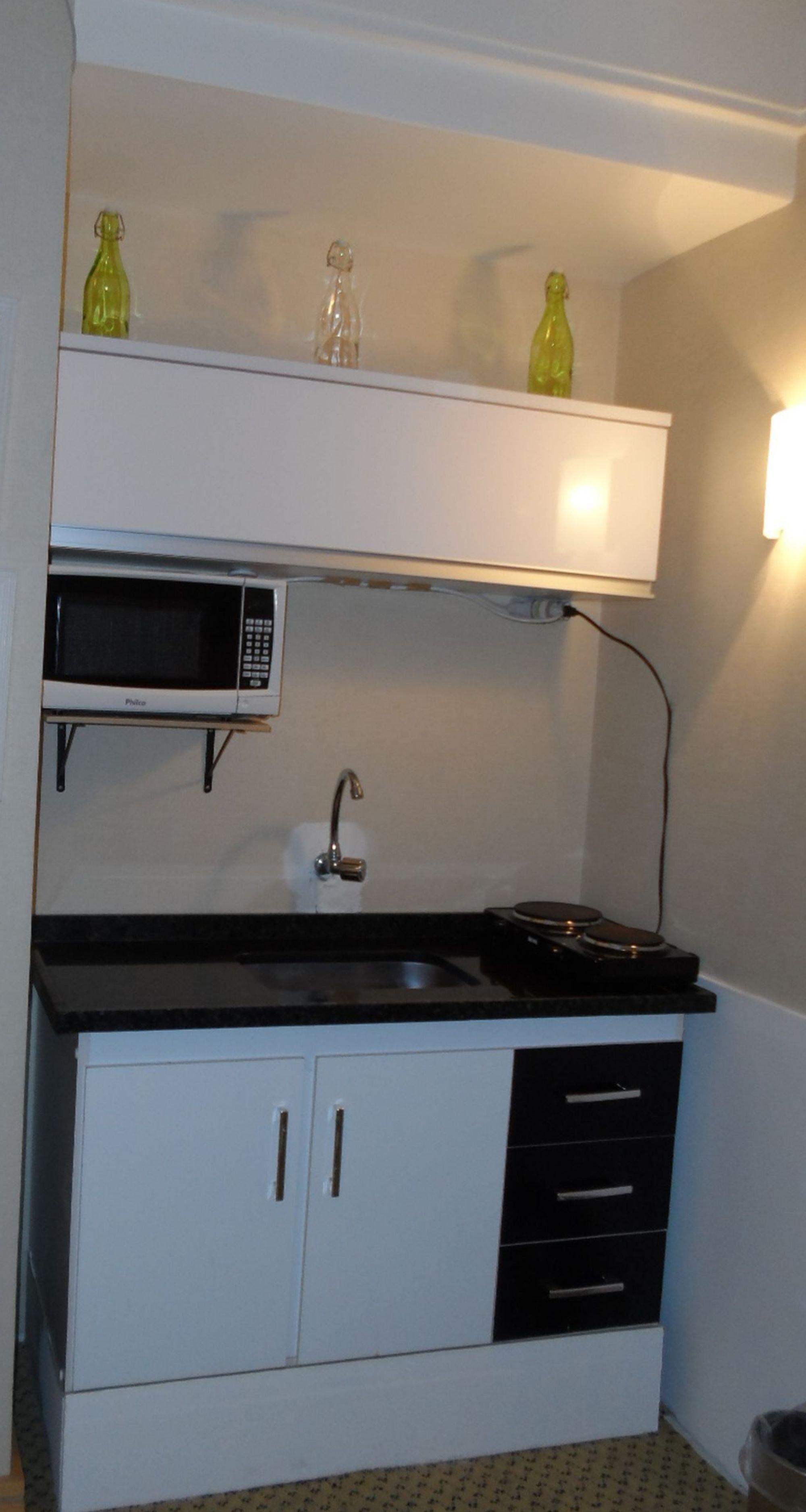 Foto de Cozinha com vaso, garrafa, pia, microondas