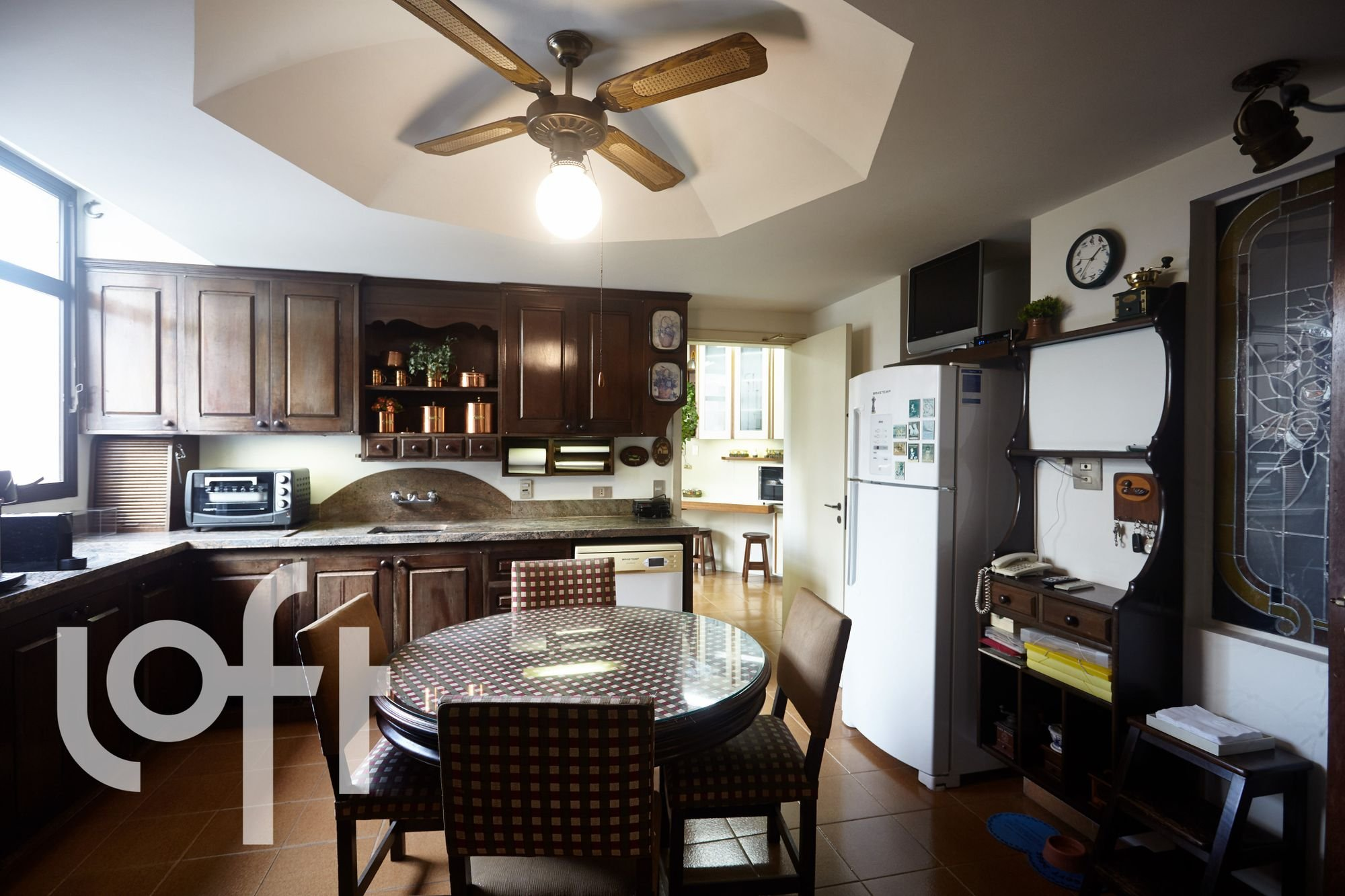 Foto de Cozinha com vaso de planta, televisão, relógio, geladeira, cadeira, mesa de jantar