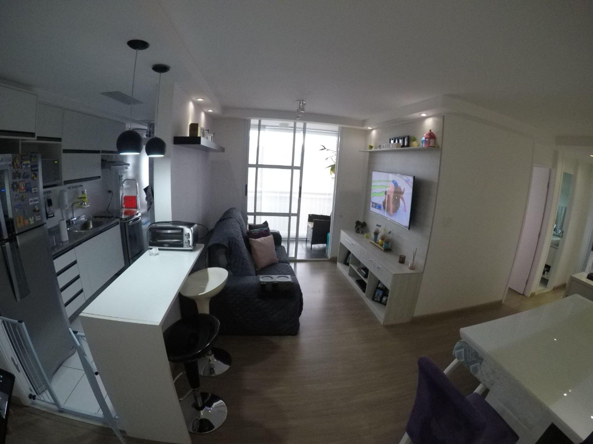 Foto de Sala com sofá, geladeira, cadeira, livro