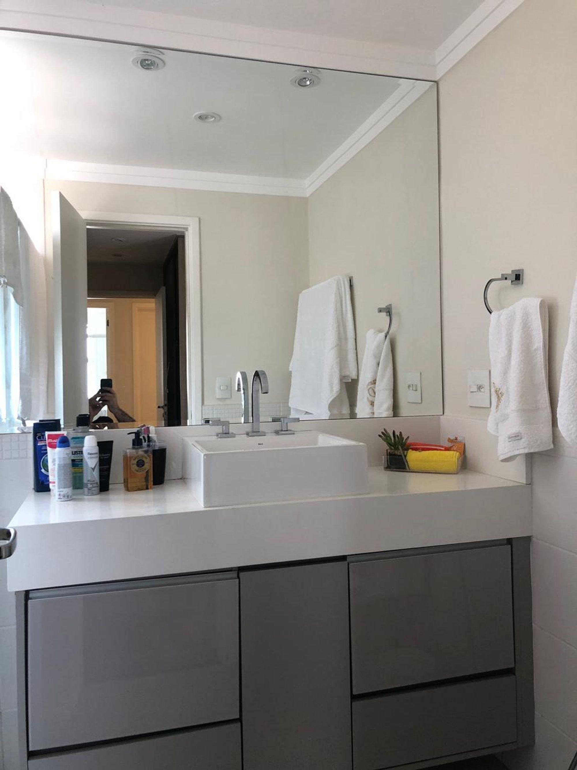 Foto de Banheiro com pessoa, pia, garrafa
