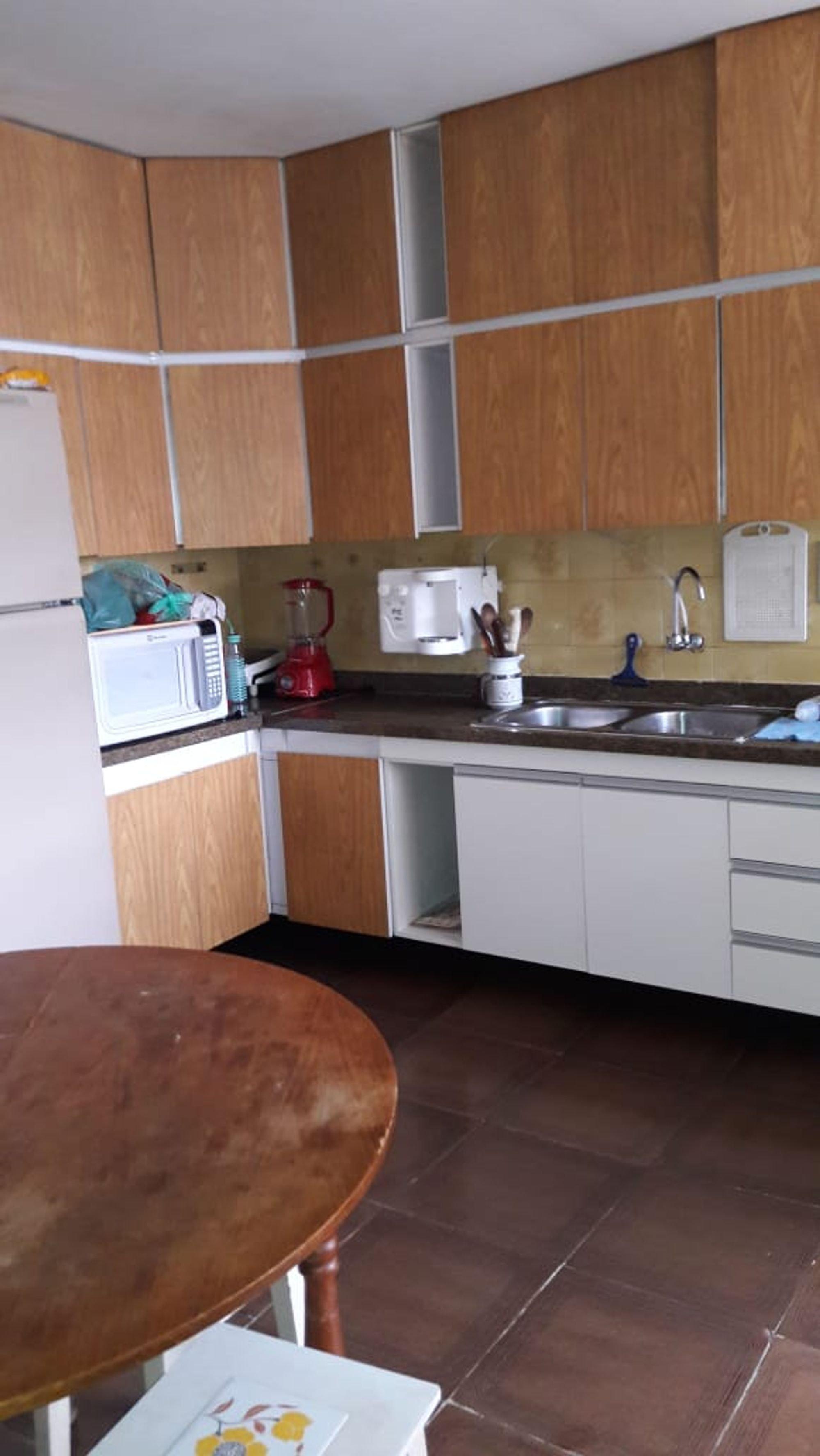 Foto de Cozinha com faca, geladeira, microondas, livro, mesa de jantar