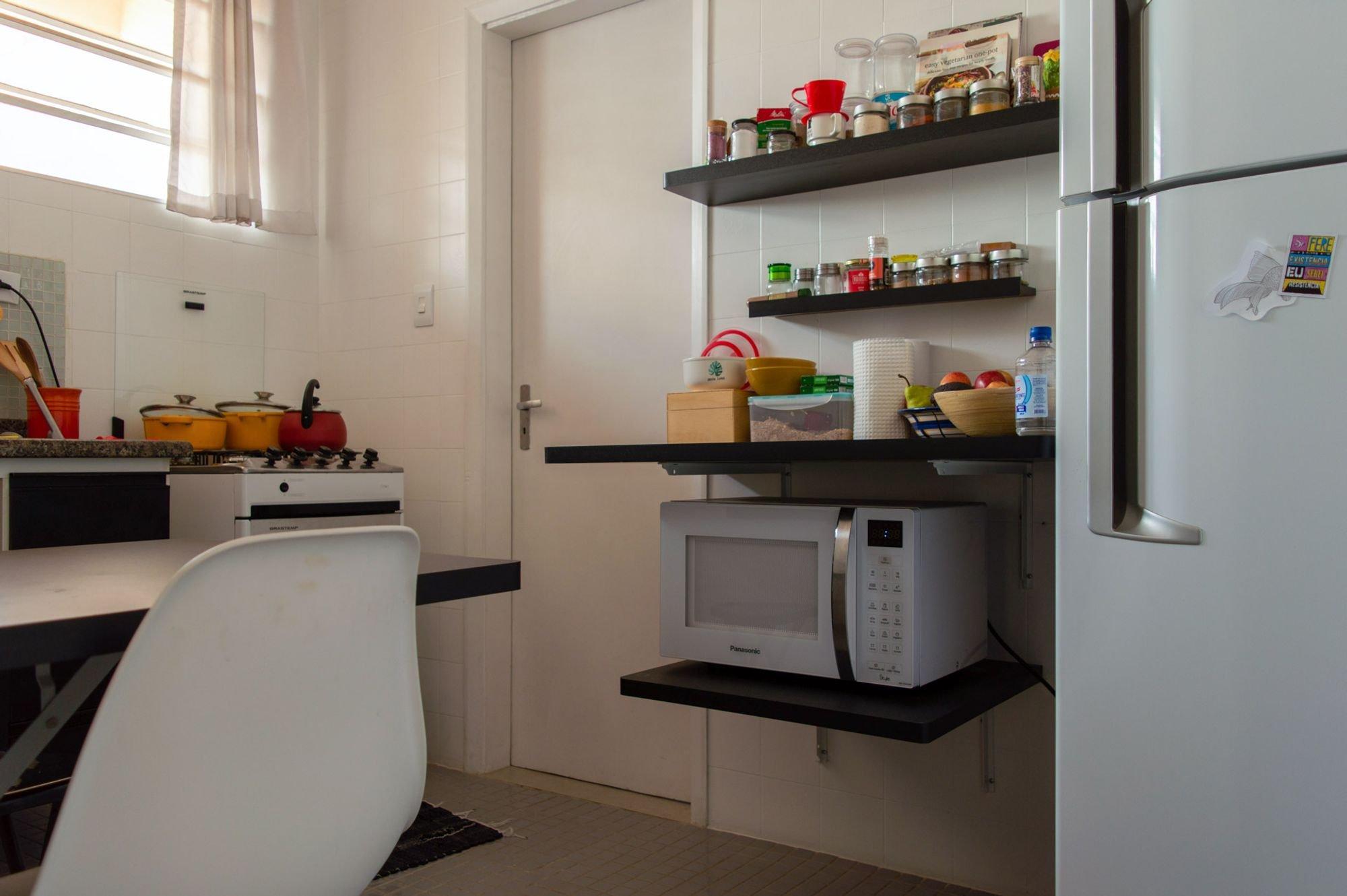 Foto de Cozinha com garrafa, tigela, geladeira, cadeira, microondas