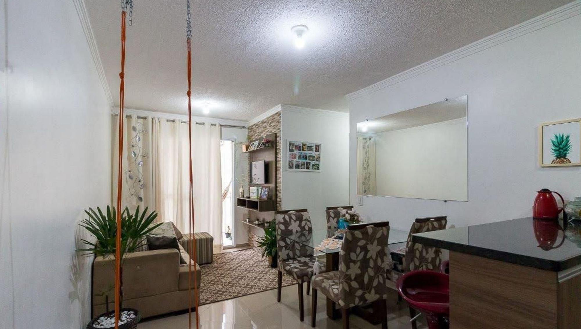 Foto de Sala com vaso de planta, sofá, televisão, cadeira, livro
