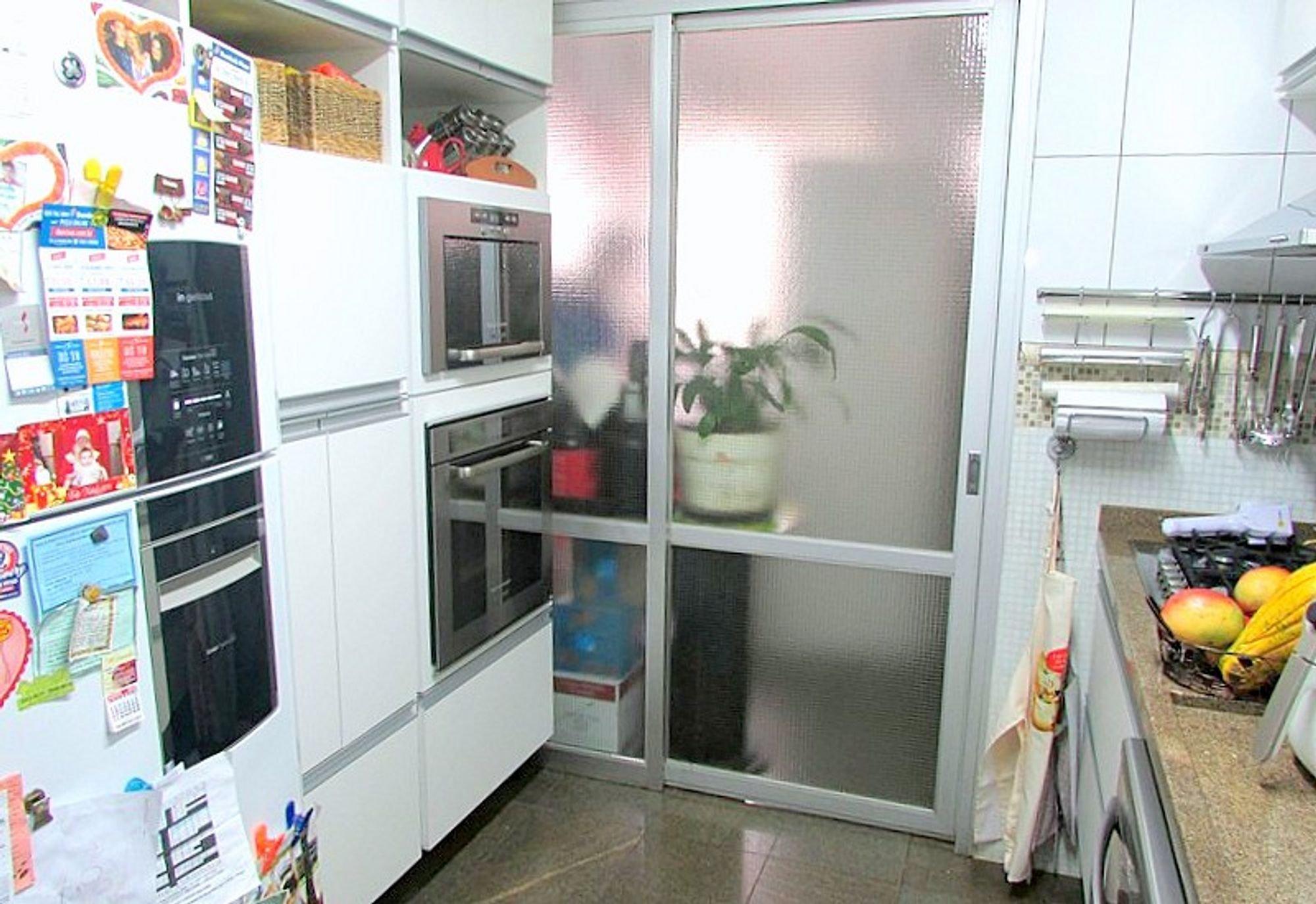 Foto de Cozinha com vaso de planta, forno, geladeira, microondas