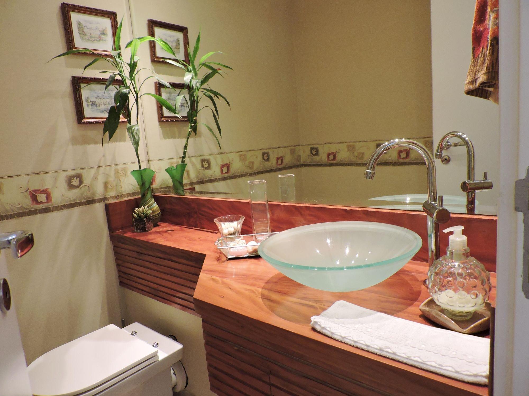Foto de Banheiro com vaso de planta, vaso sanitário, pia, vaso, garrafa, tigela, xícara