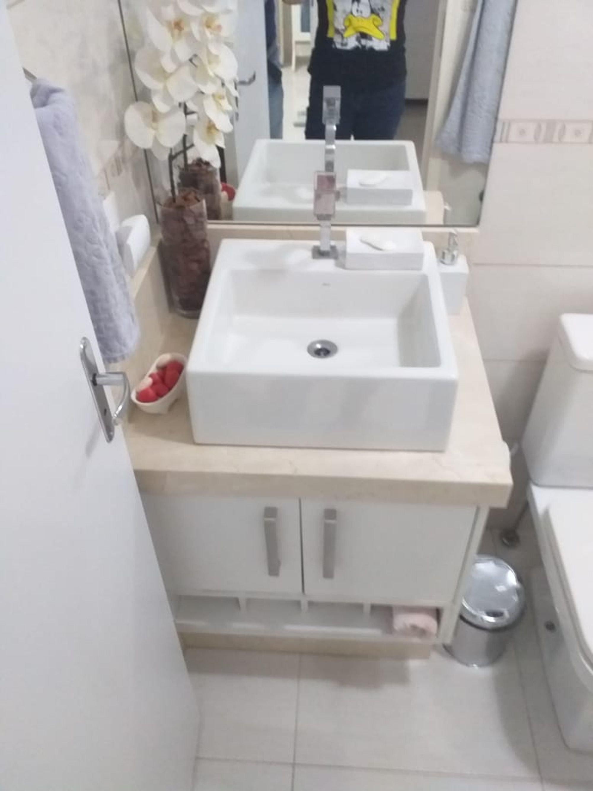 Foto de Banheiro com vaso sanitário, pia, pessoa