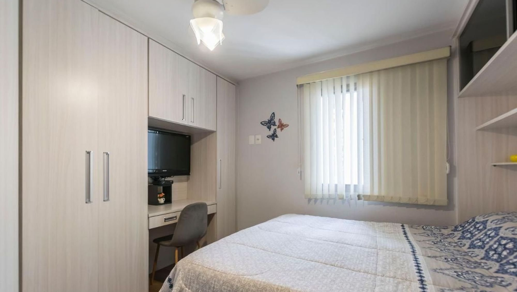 Foto de Quarto com cama, televisão, cadeira