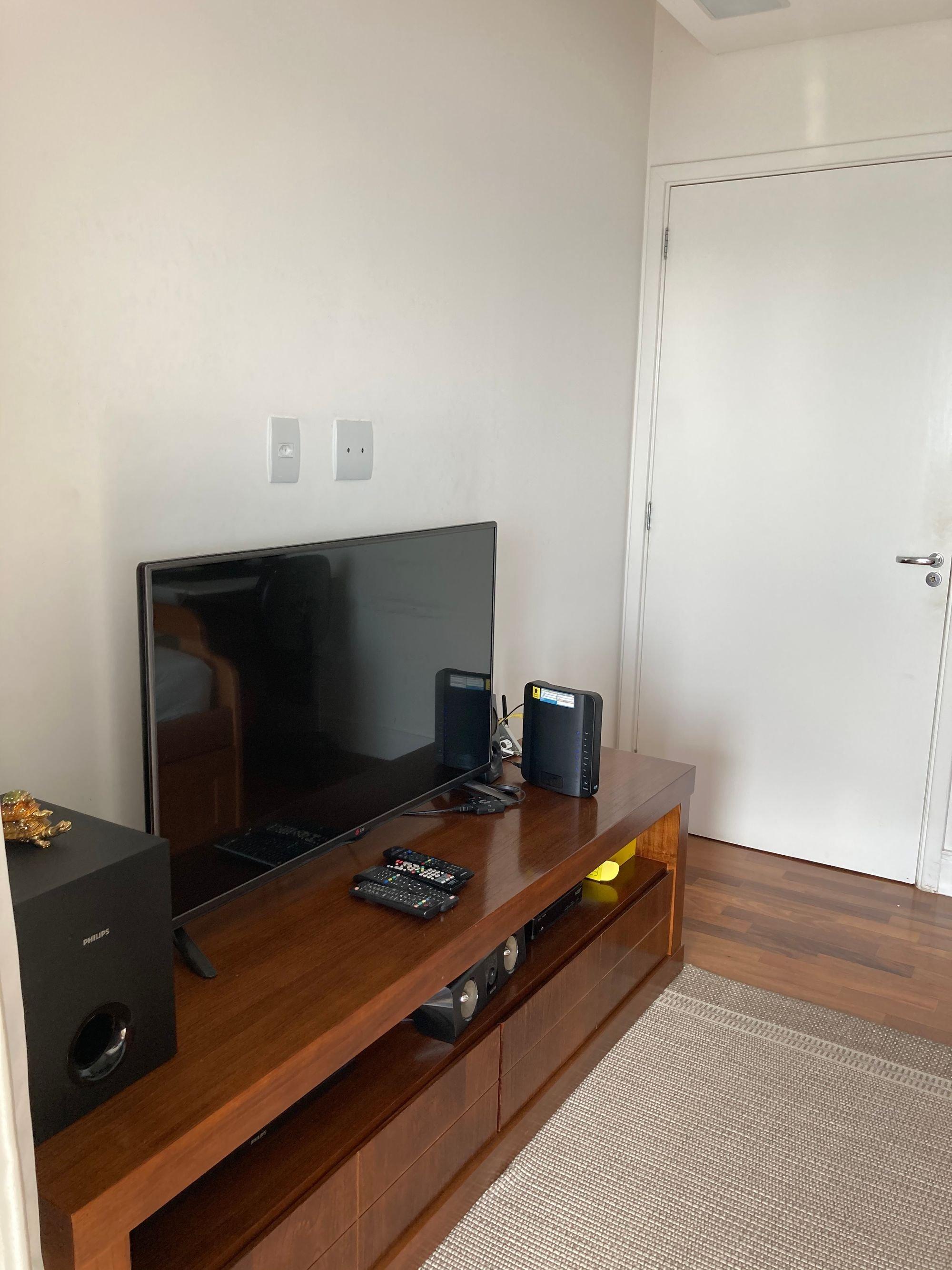 Foto de Sala com controle remoto, televisão, relógio