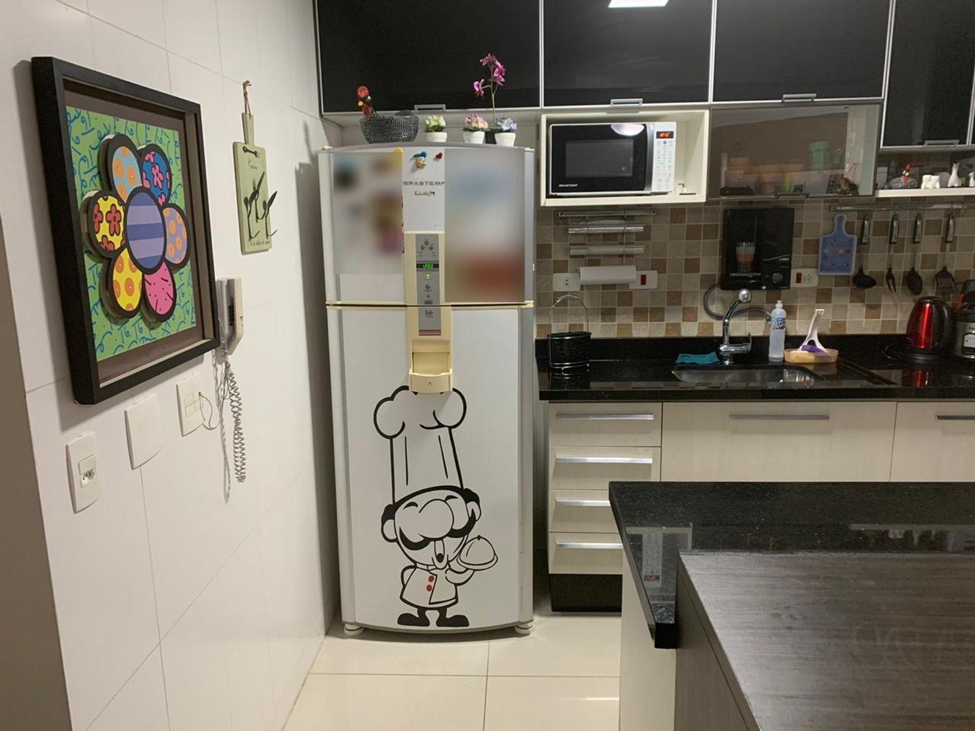 Foto de Cozinha com garrafa, tigela, geladeira, pia, microondas
