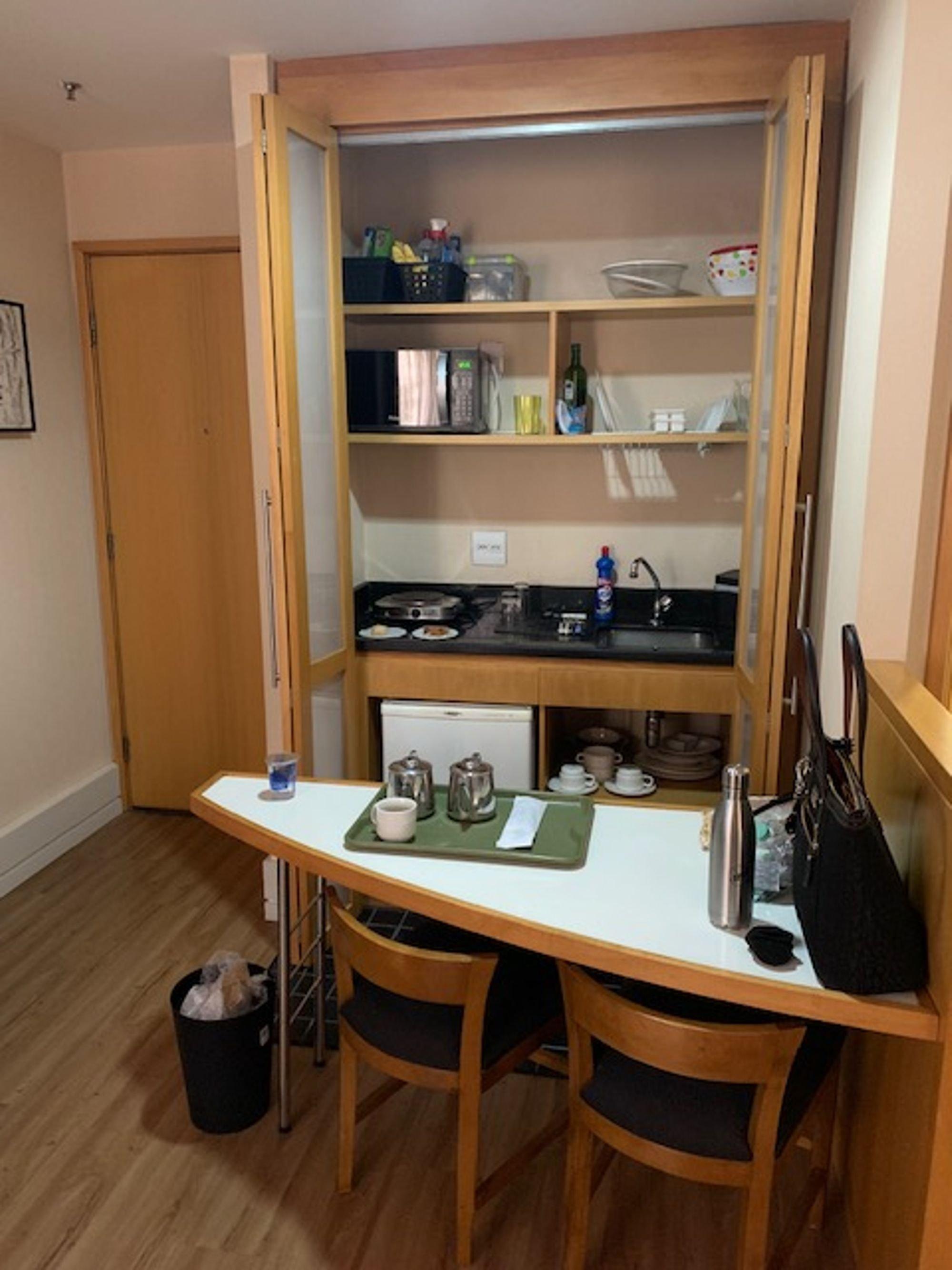 Foto de Sala com bolsa, pia, cadeira, mesa de jantar, garrafa, tigela, xícara