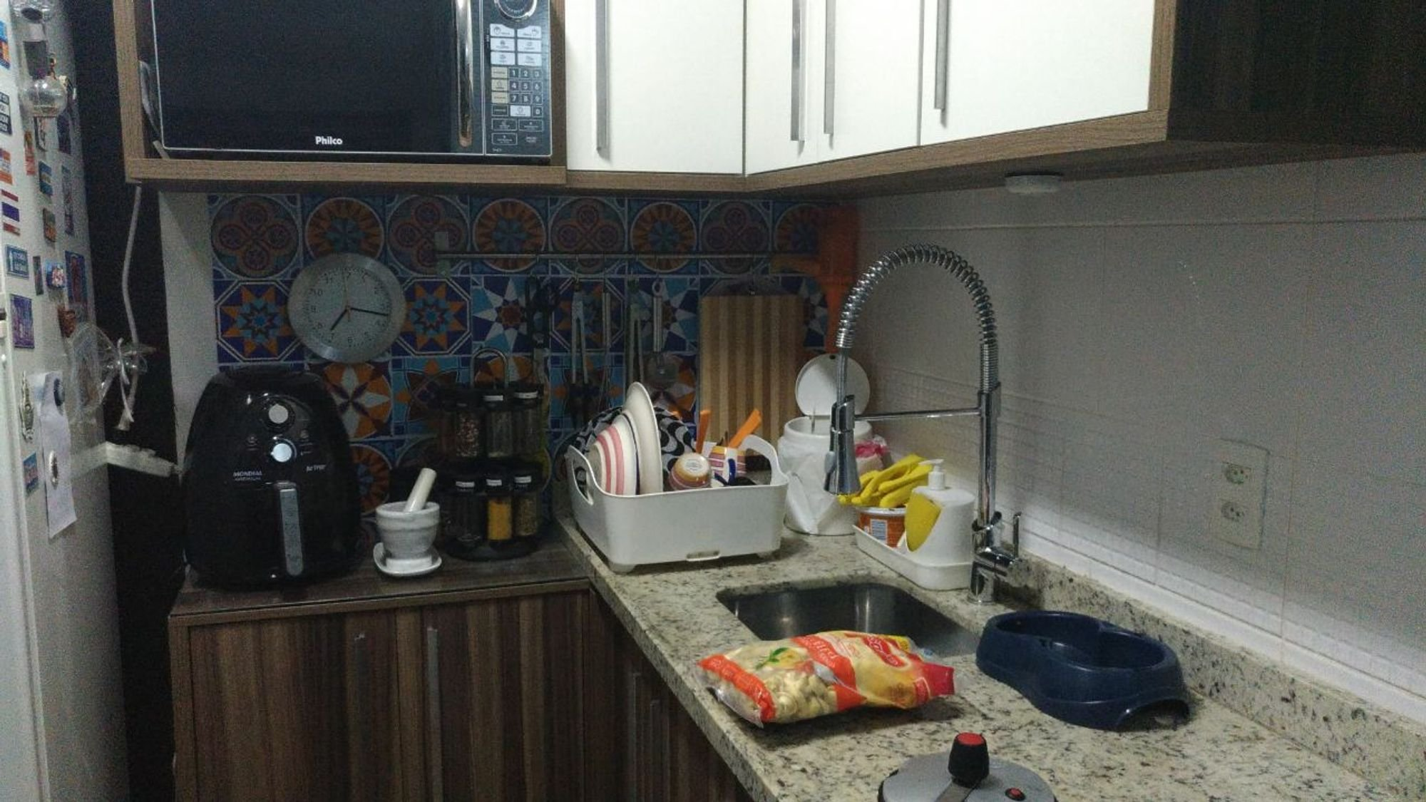 Foto de Cozinha com relógio, pia, microondas, xícara