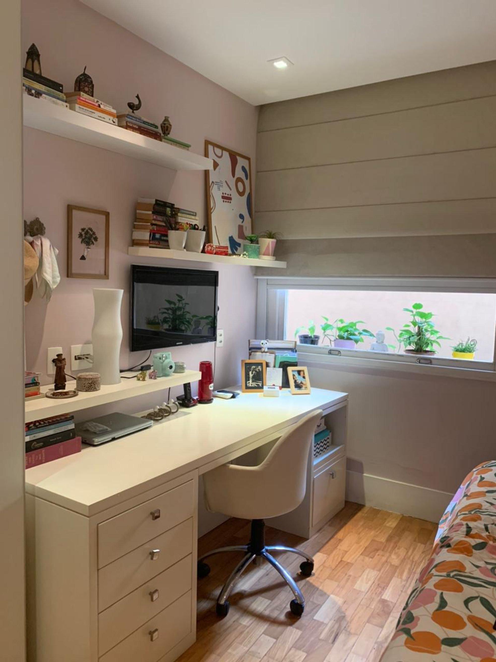 Foto de Quarto com vaso de planta, televisão, cadeira, livro, sofá, vaso, tigela