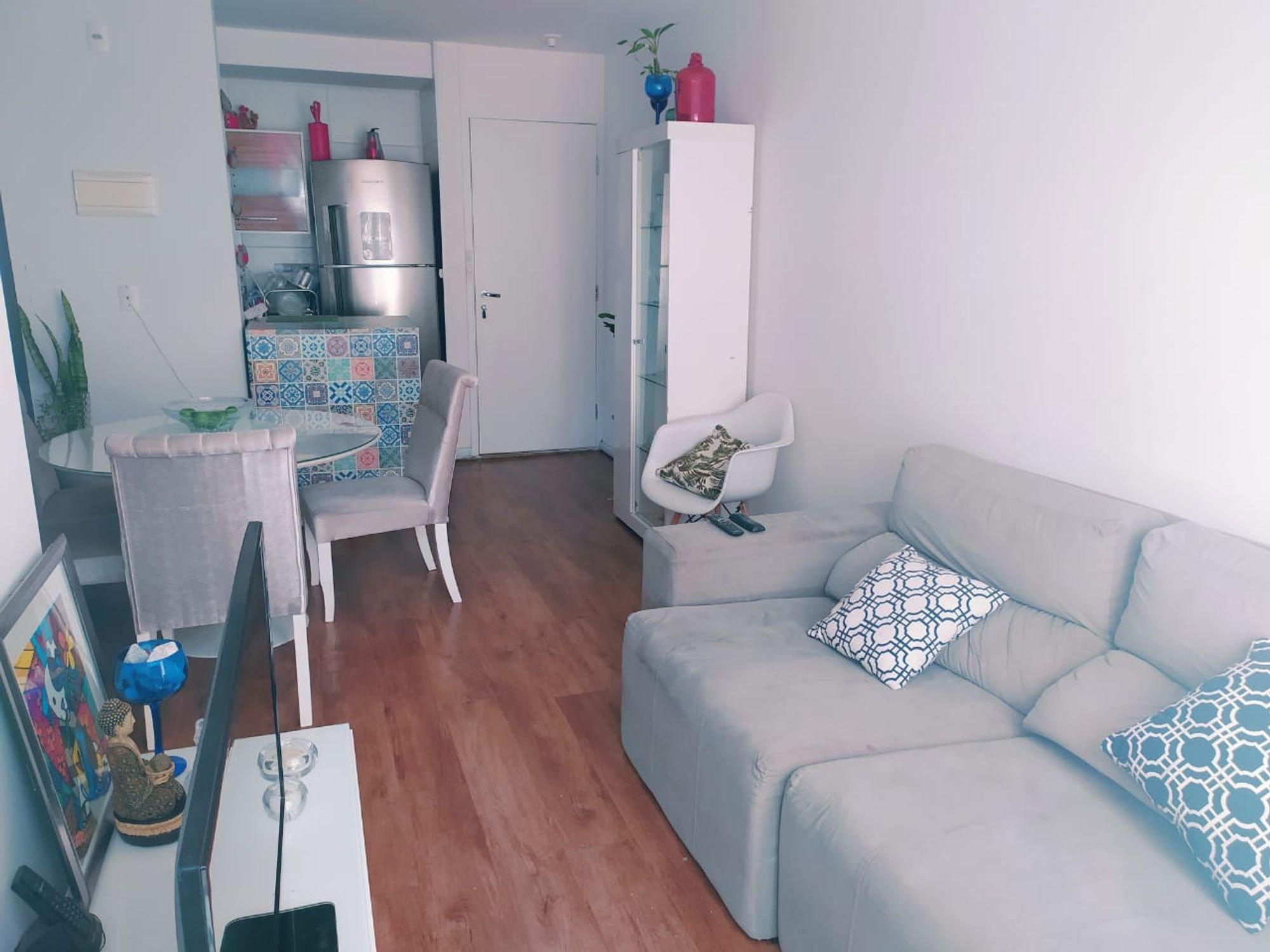 Foto de Sala com vaso de planta, maçã, cadeira, sofá, garrafa, tigela, geladeira