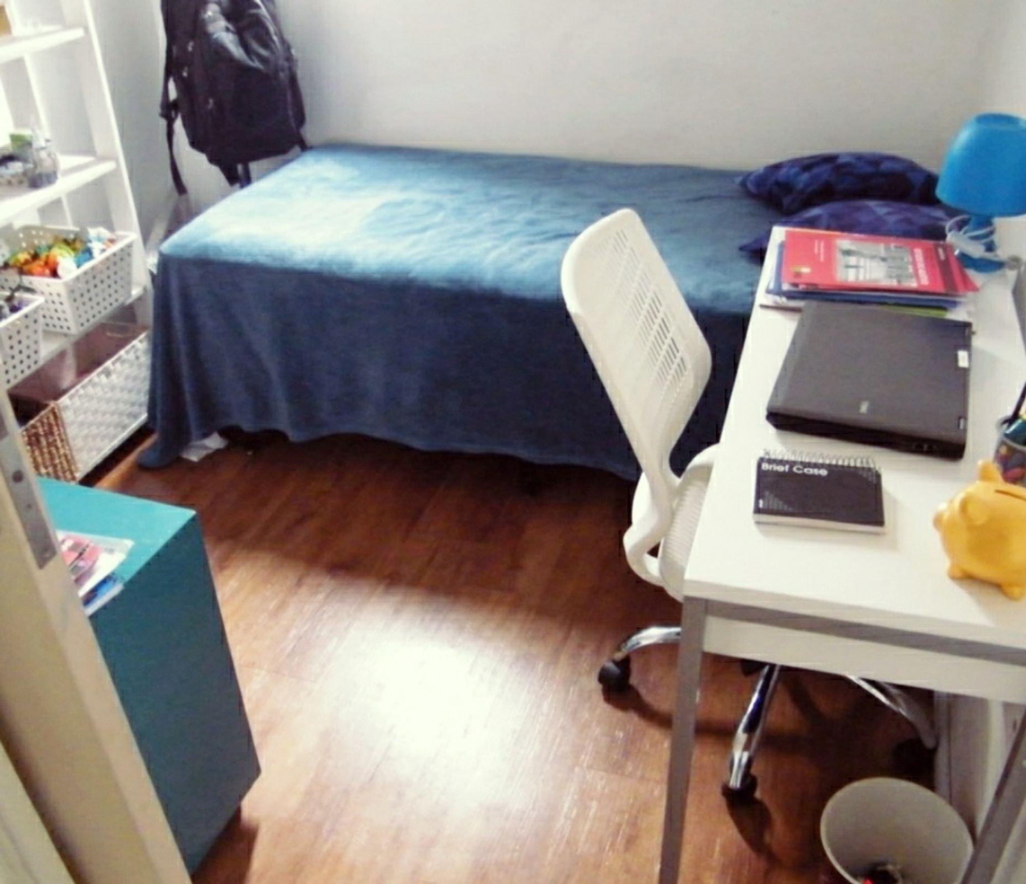 Foto de Quarto com cama, computador portátil, mochila, mesa de jantar, livro