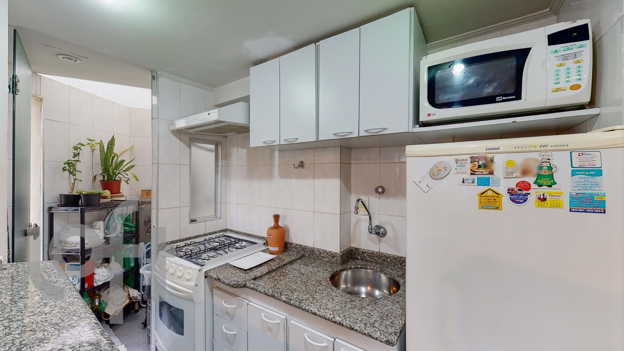 Foto de Cozinha com vaso de planta, garrafa, forno, geladeira, pia, microondas
