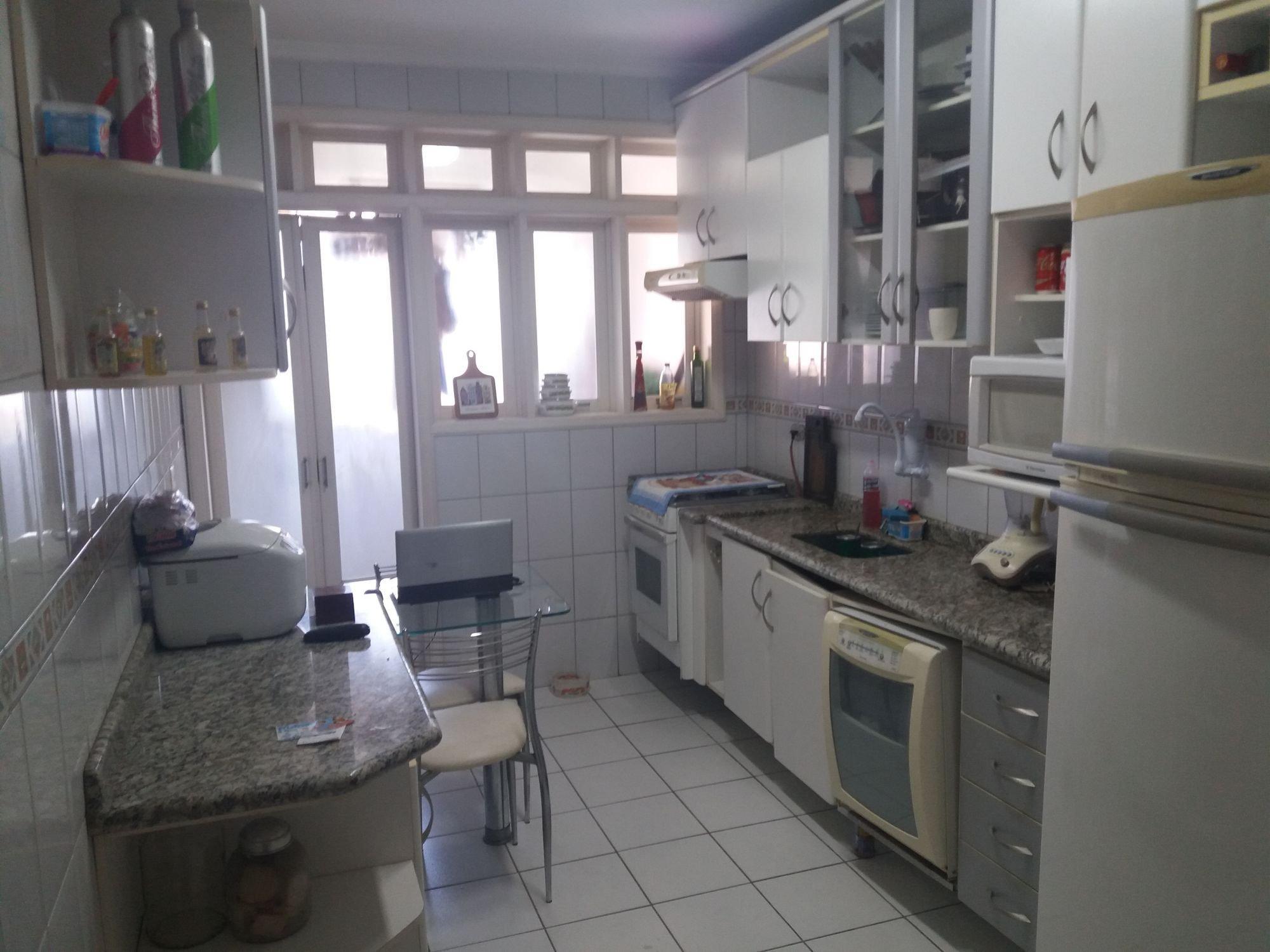 Foto de Cozinha com forno, pia, cadeira, garrafa, tigela, geladeira, microondas