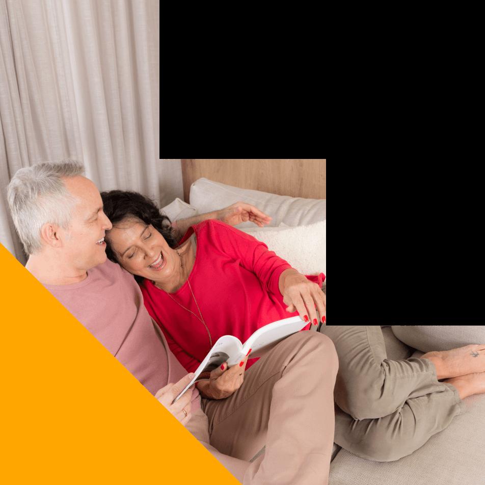 Um casal deitados e abraçados lendo um livro e rindo juntos